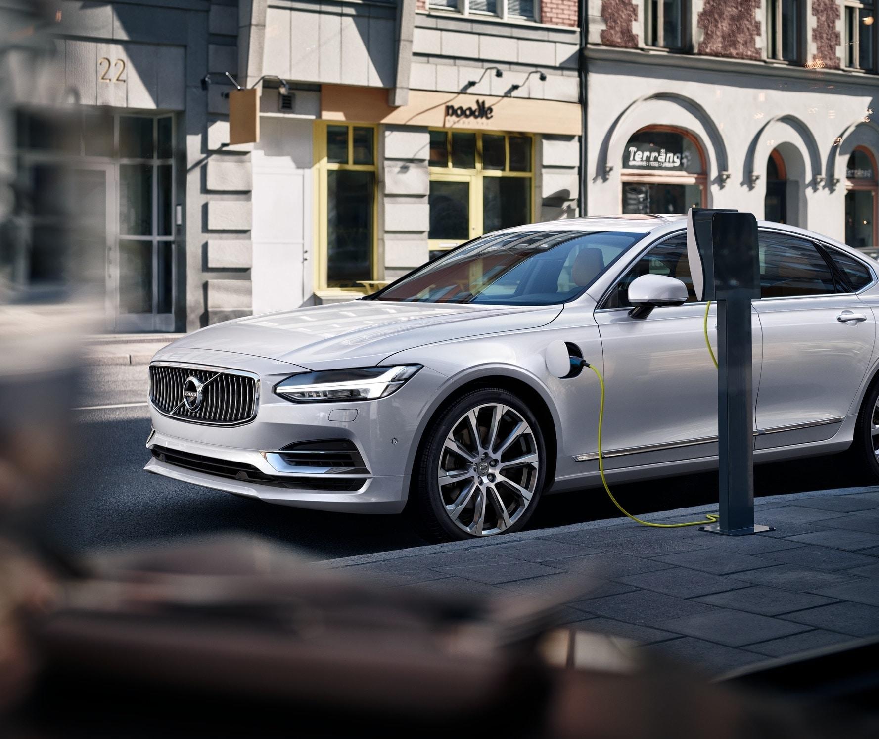 Foto do Volvo S90, sedan de luxo, carregando em um posto de carregamento na rua.