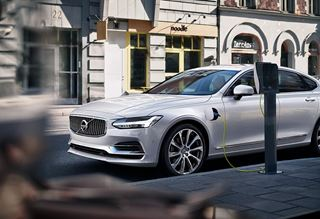 Der Volvo S90 T8 TWIN ENGINE AWD INSCRIPTION - Crystal White - Frontansicht - Fahrzeug an Ladestation