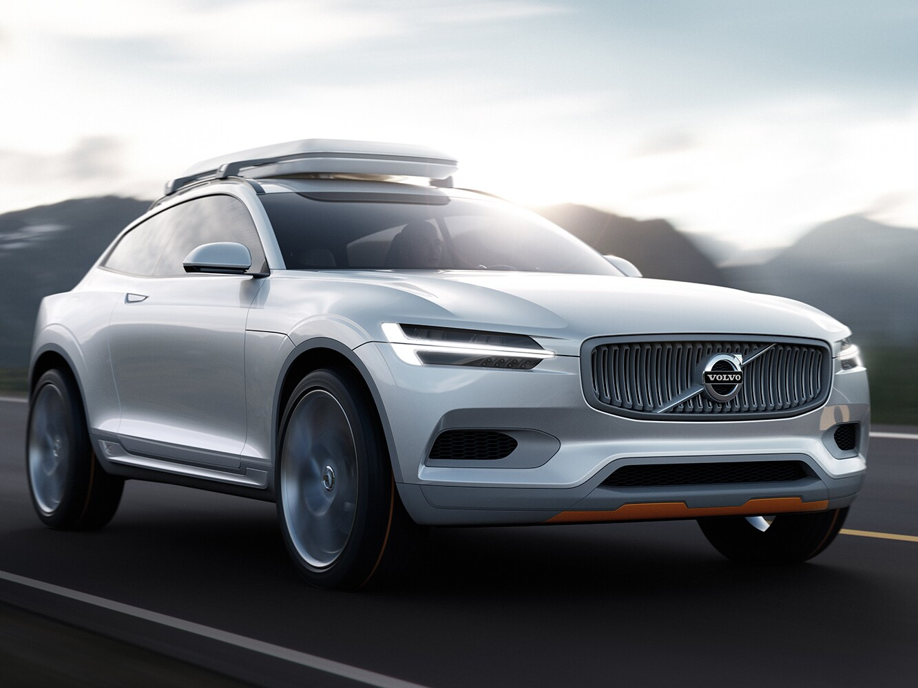 The Volvo Concept XC travels along a freeway with mountains behind it.