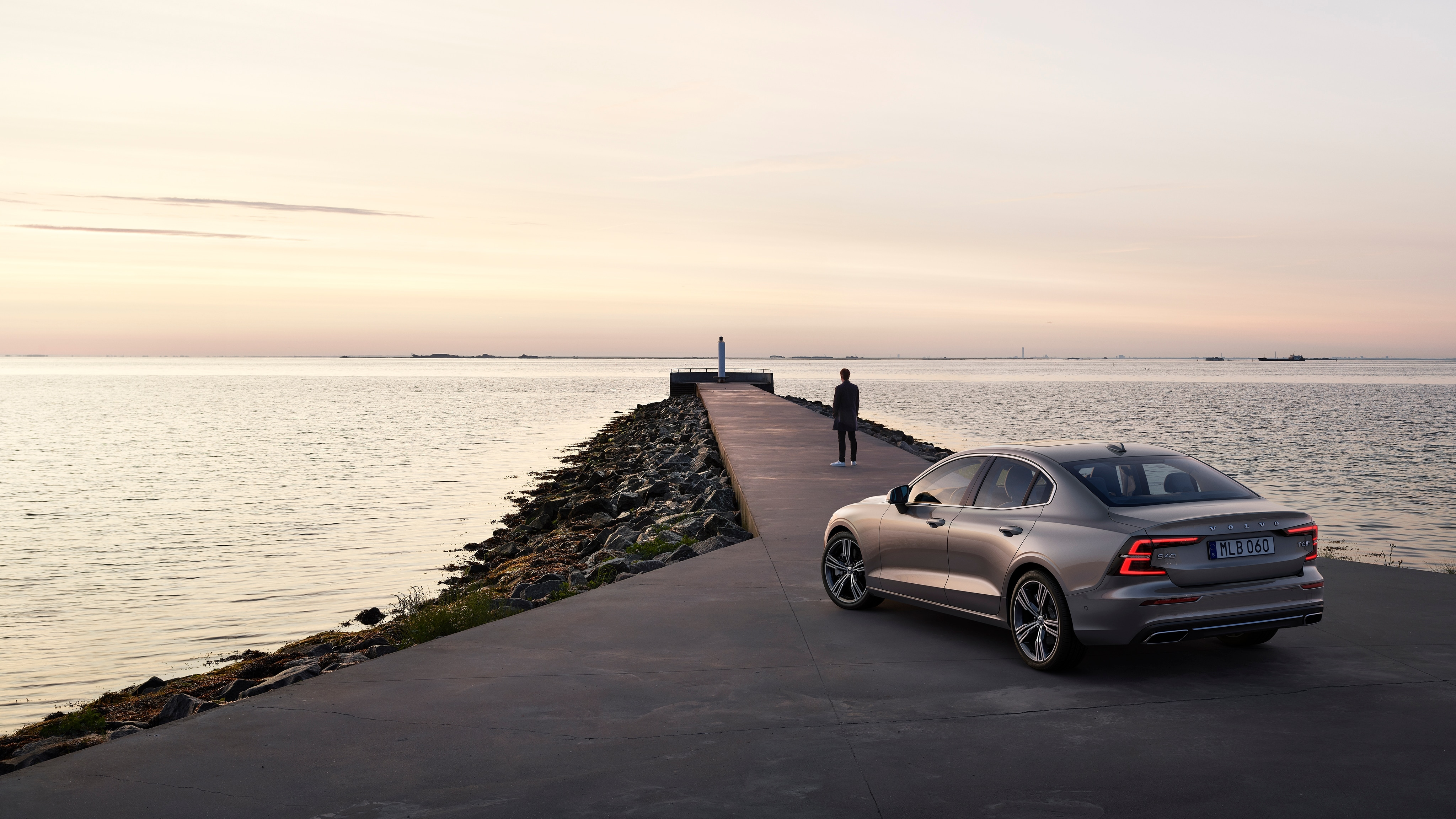 A man looks out to sea, with his Volvo S60 Inscription parked behind him