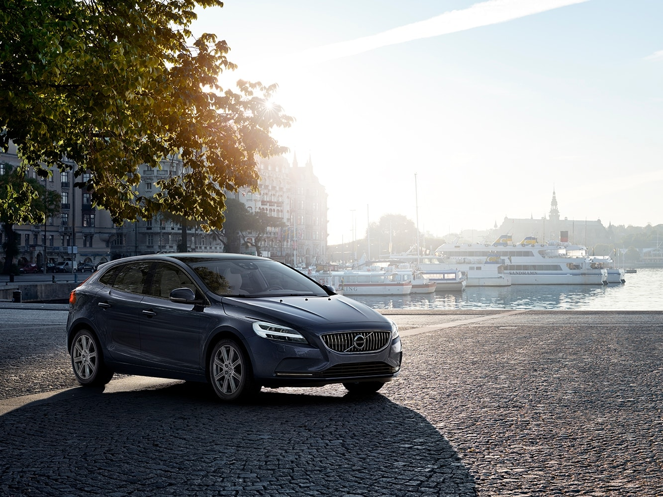 The Volvo V40 standing next to the ocean with the sunset in the backround