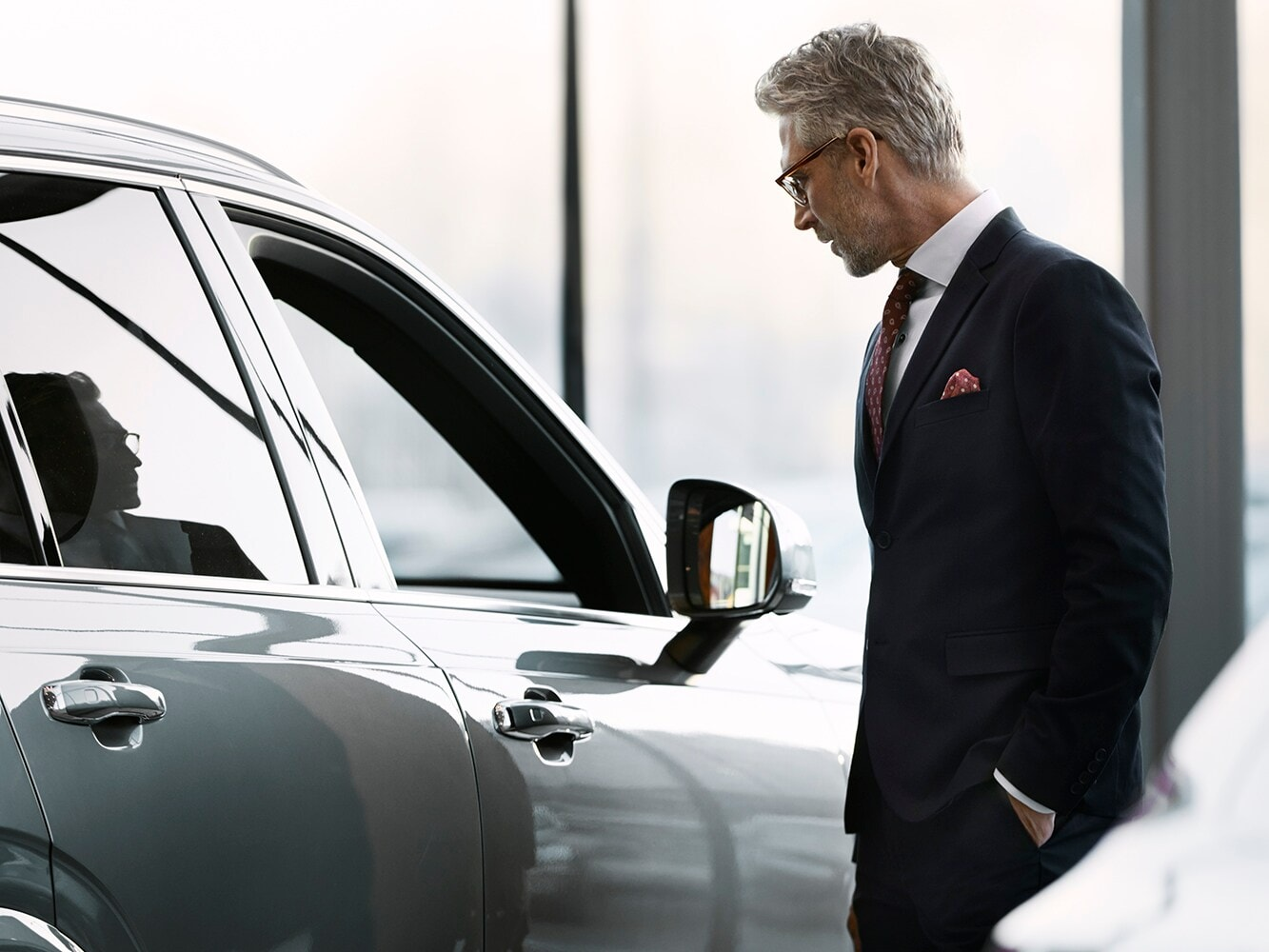 Close up side view of a man in a suit looking into the Volvo V40 passenger window