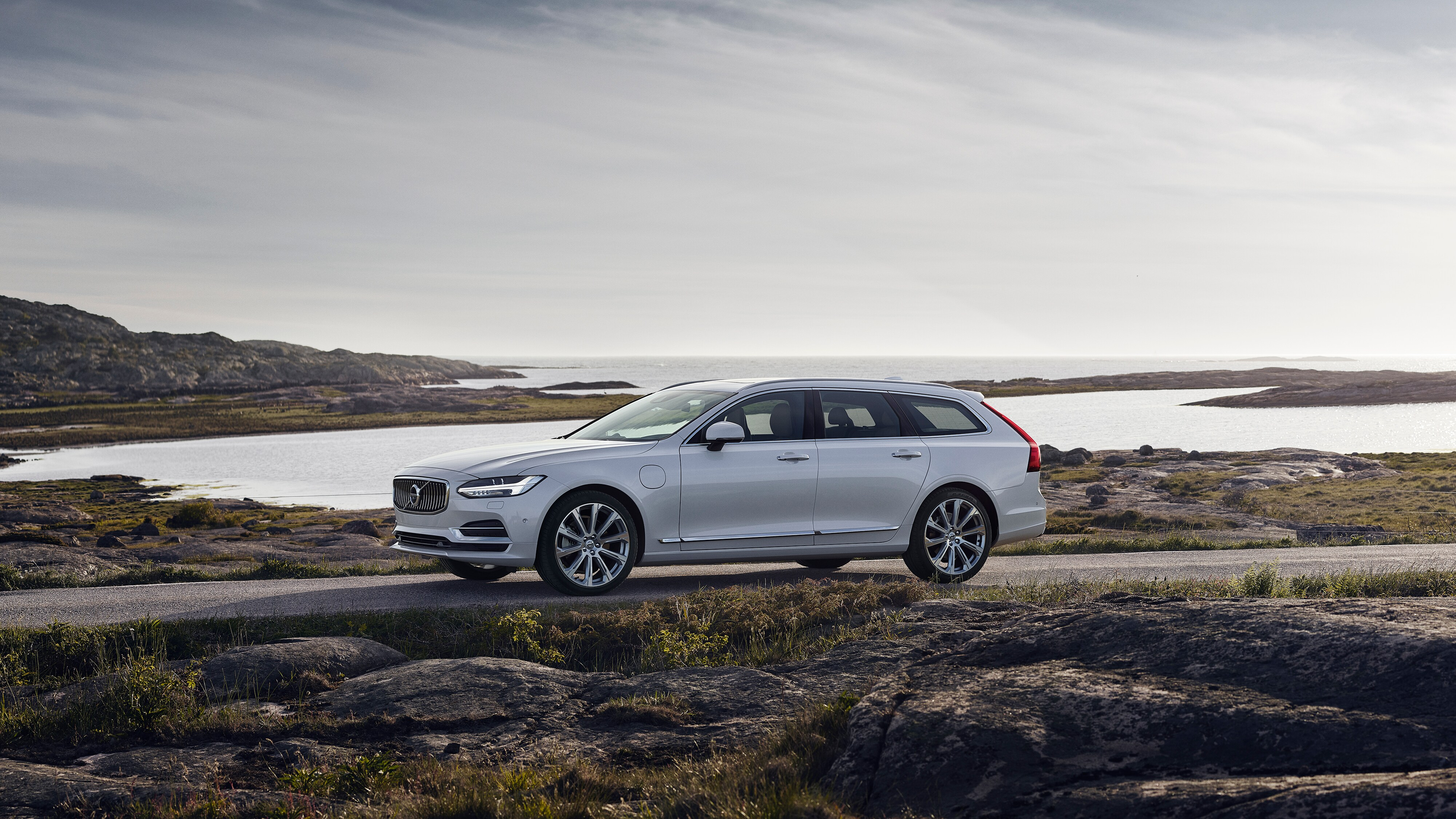 Side view of a white Volvo V90 on a road near the sea