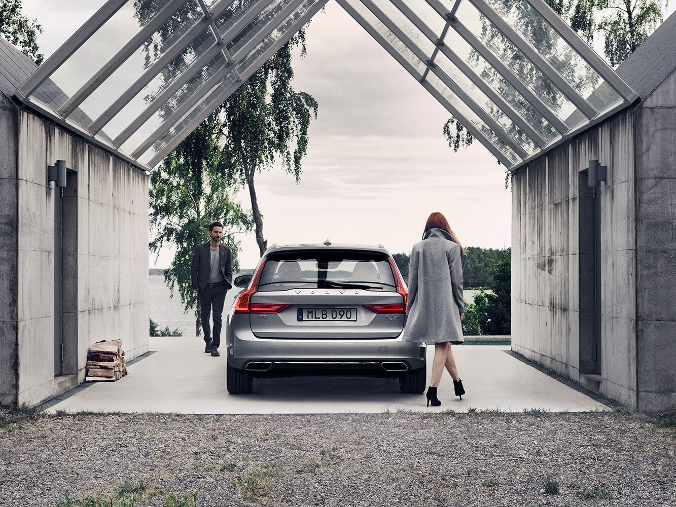 Volvo V90 in glass-roofed parking bay with woman approaching