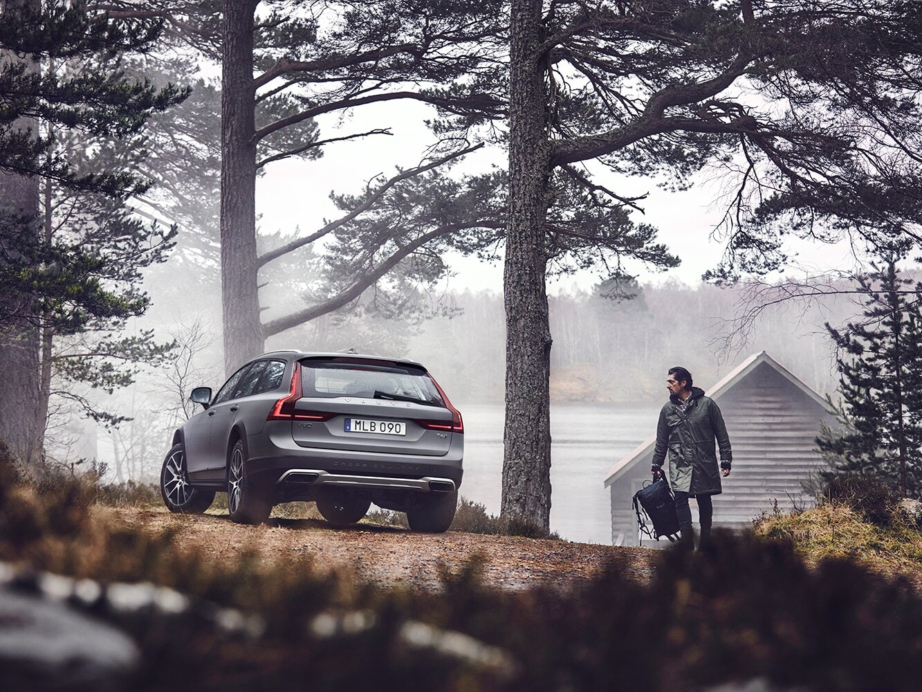 Rear view of a Volvo V90 in a misty forest