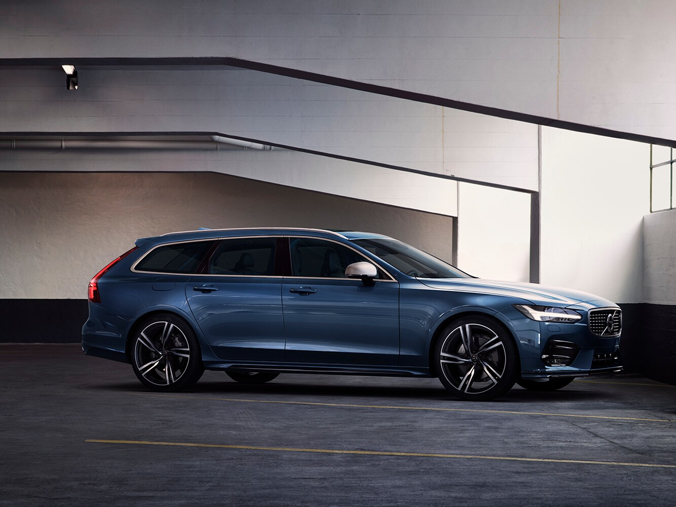 Side-front view of Volvo V90 R-Design in carpark showing of the stiffer, lowered Sport Chassis.
