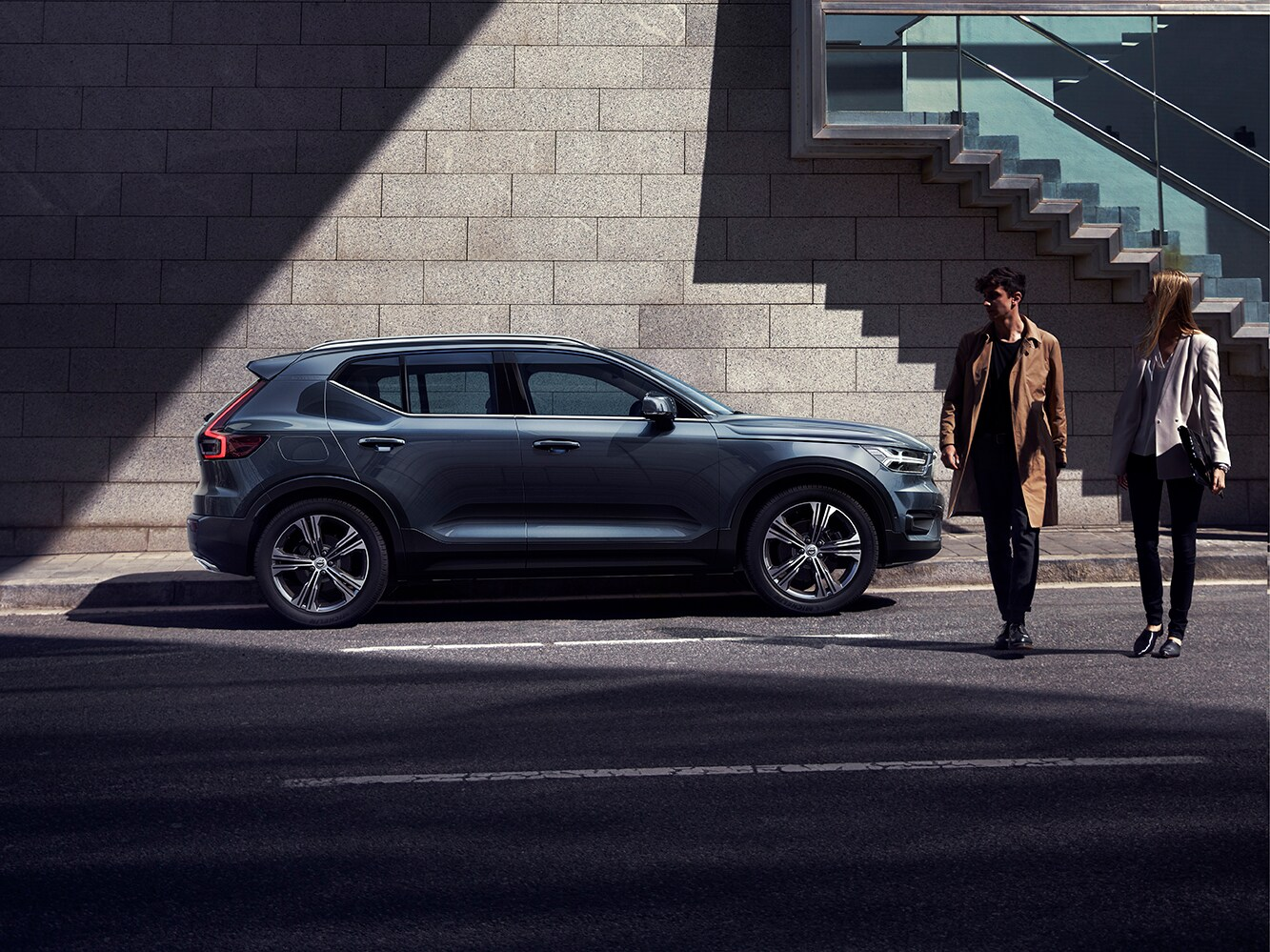 The luxurious Volvo XC40 Inscription parked on a street with two young people