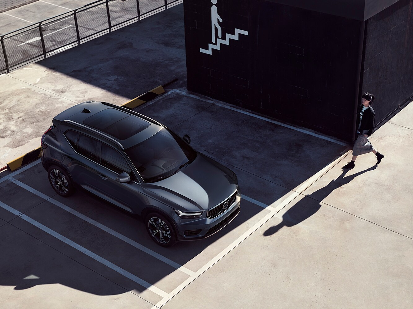 A dark grey Volvo XC40 R-Design trim parked in the shadow of a building