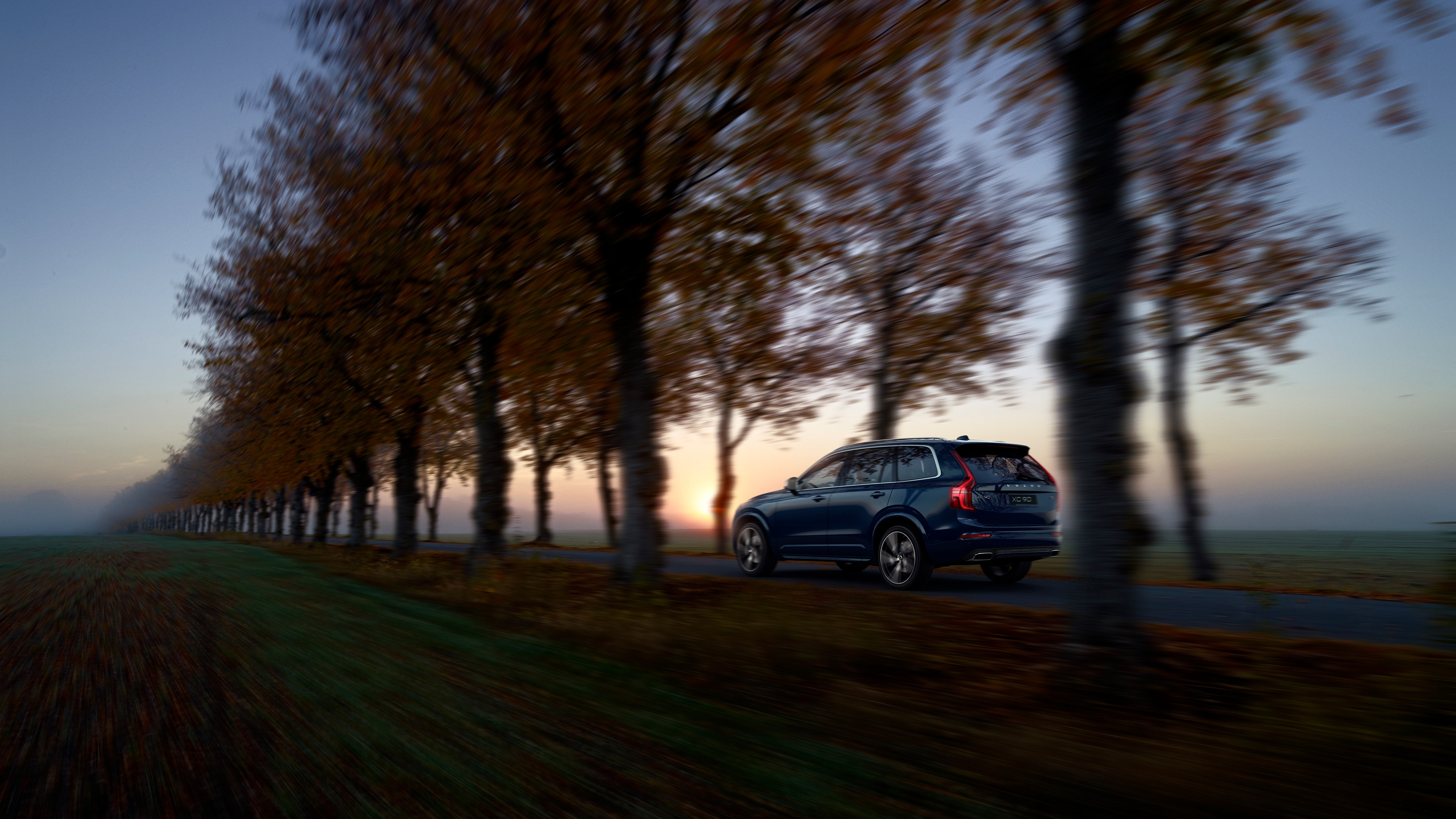 Side rear view of a Volvo XC90 R-Design travelling down a tree-lined road