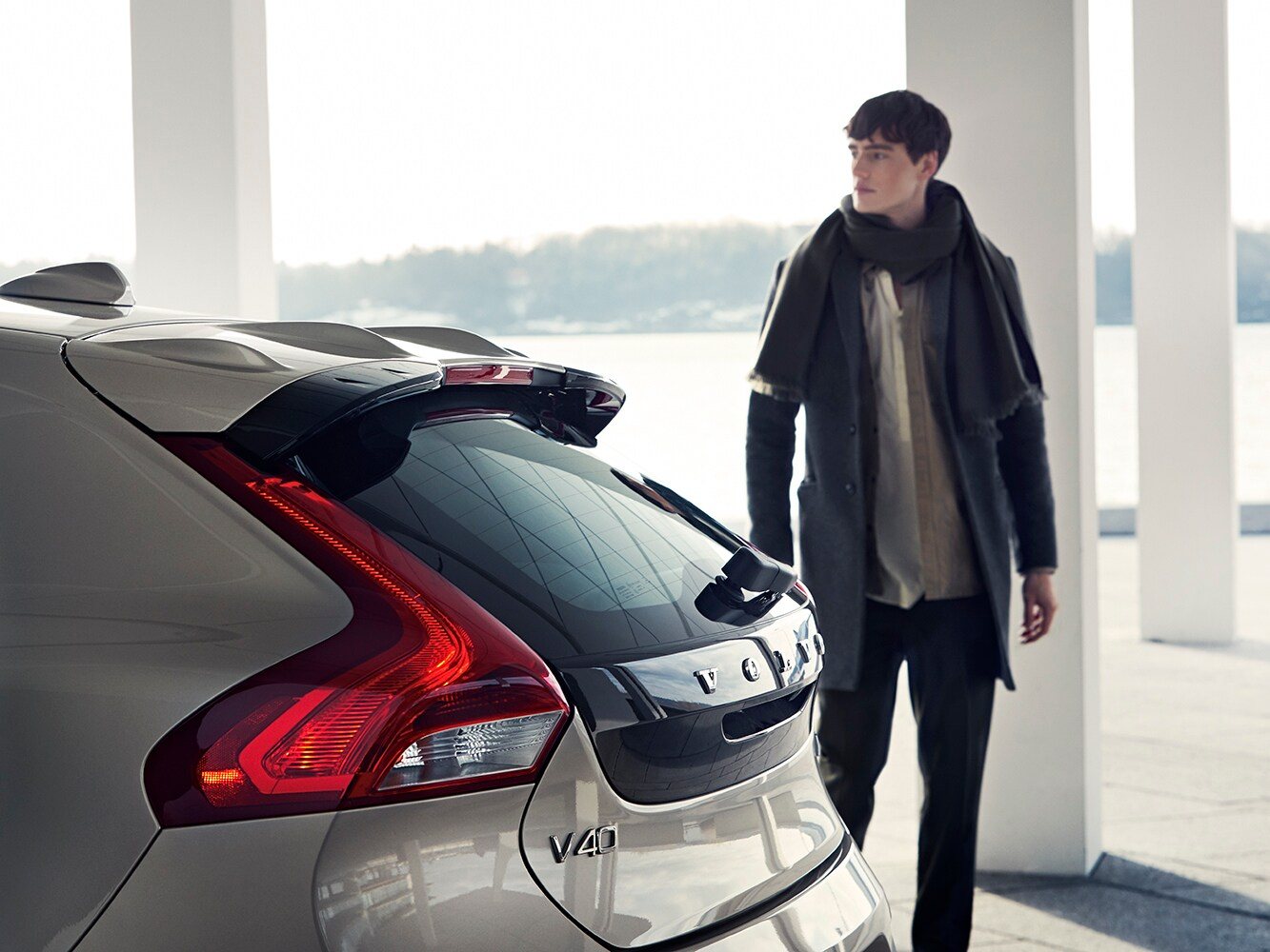 Rear side view of the Volvo V40 and a man approaching the vehicle