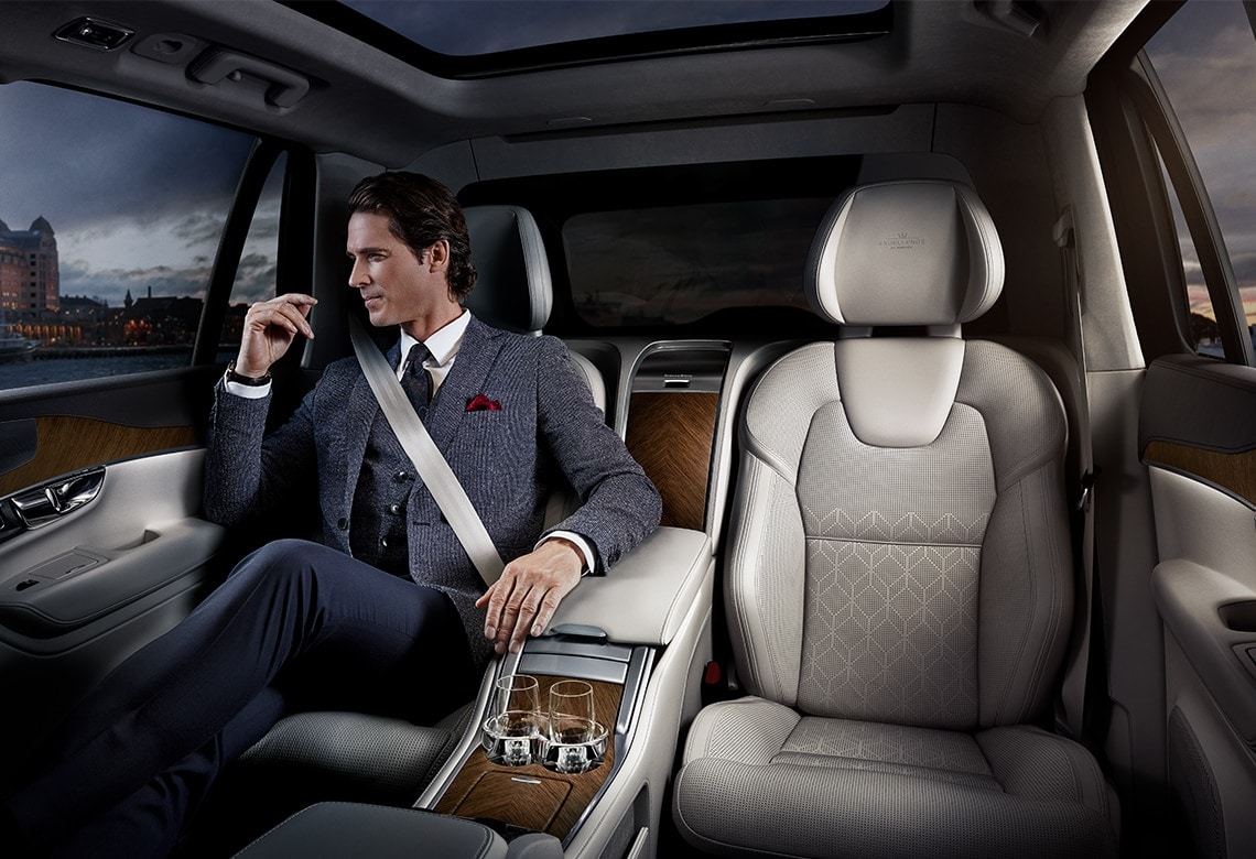 A man reclines in the sophisticated rear passenger seat in the Volvo XC90 Excellence