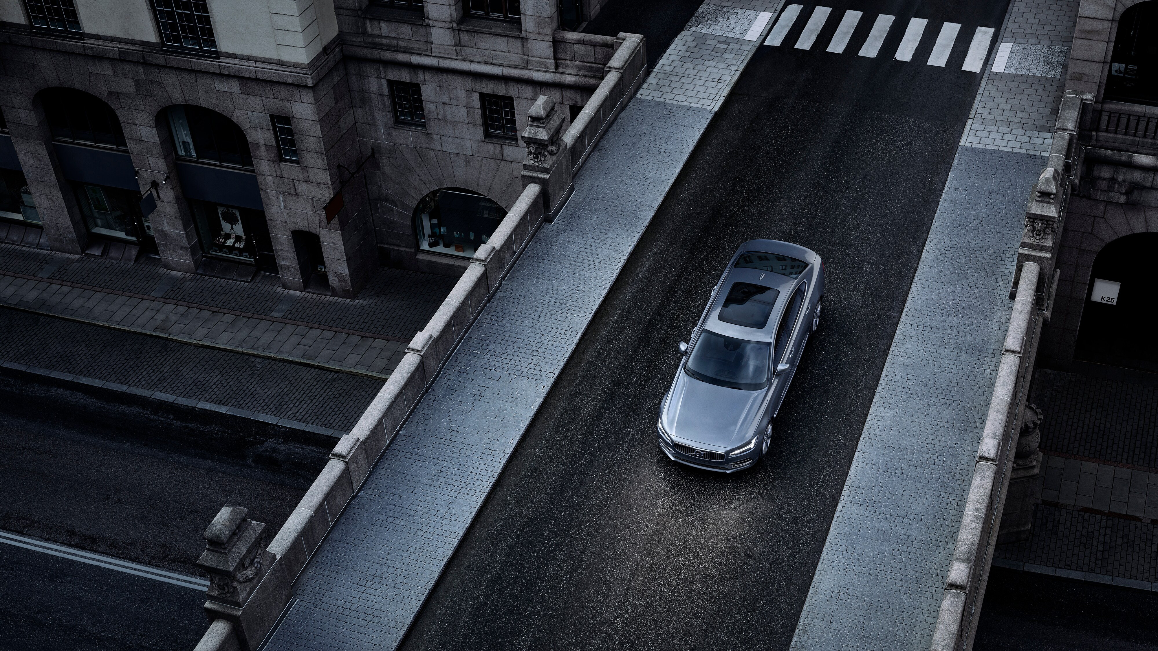 Aerial view of a Volvo S90 driving across an overpass in the city