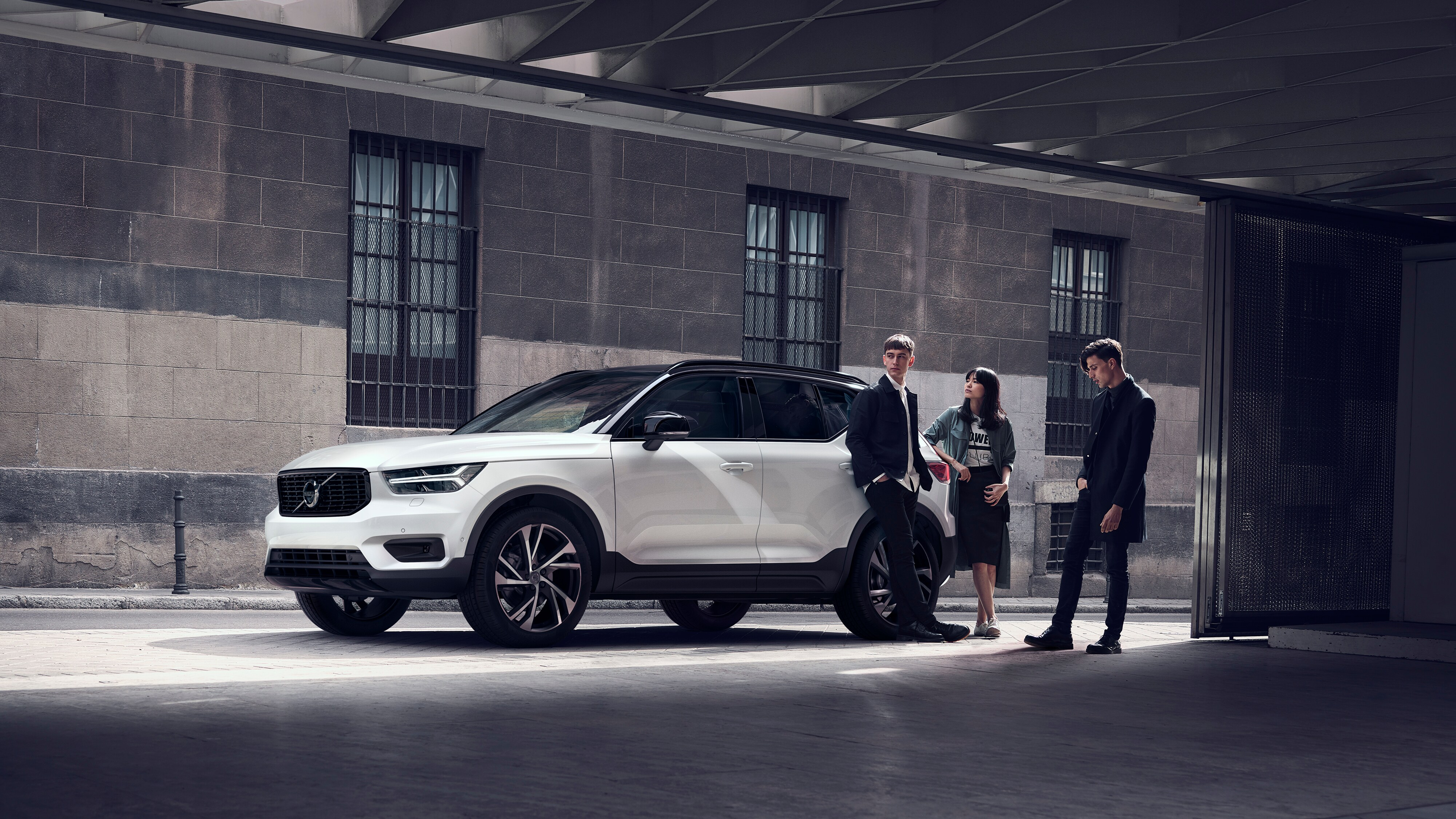 A Volvo XC40 R-Design parked in an urban environment with three young people