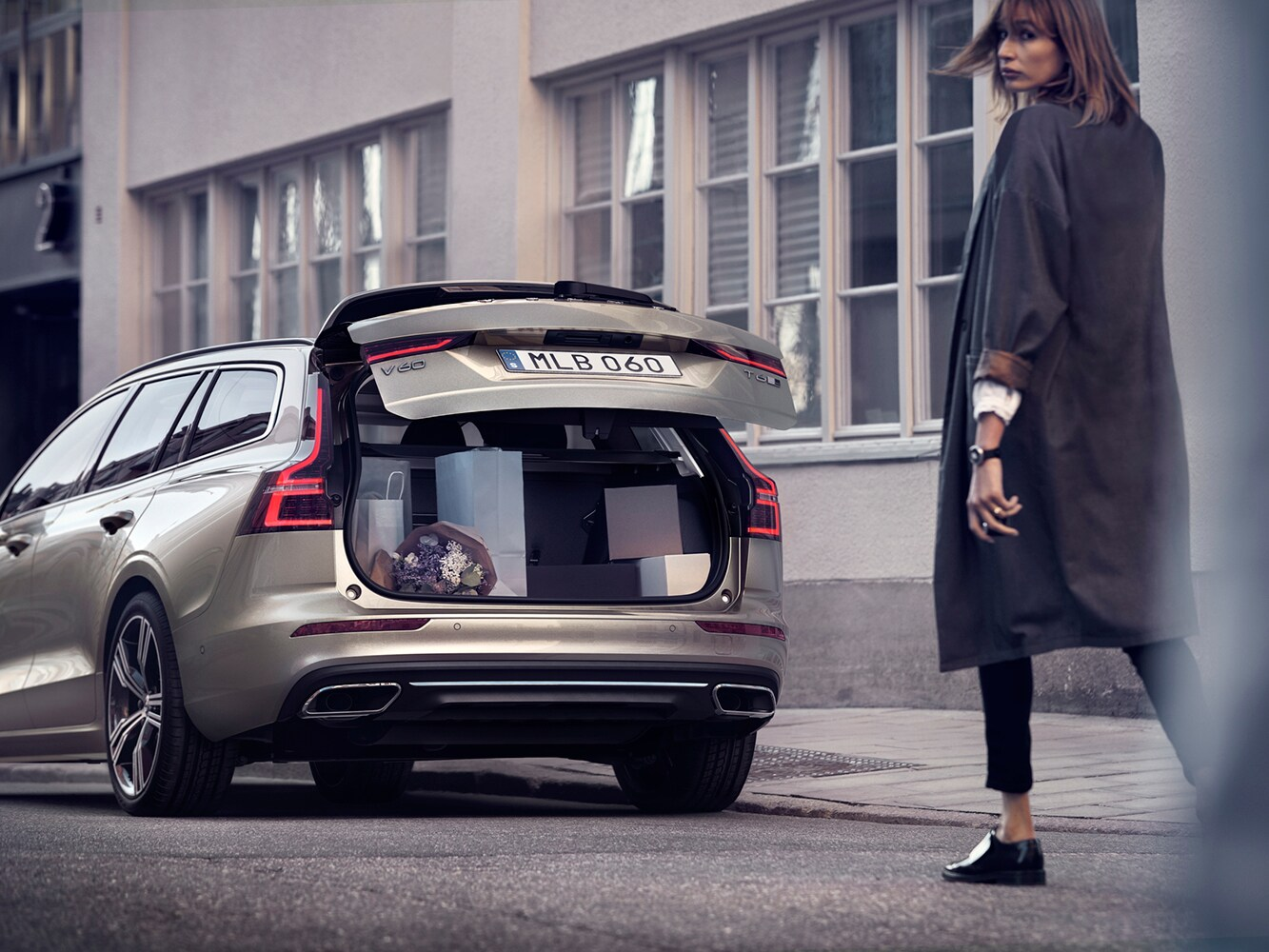 Woman walking towards parked Volvo V60