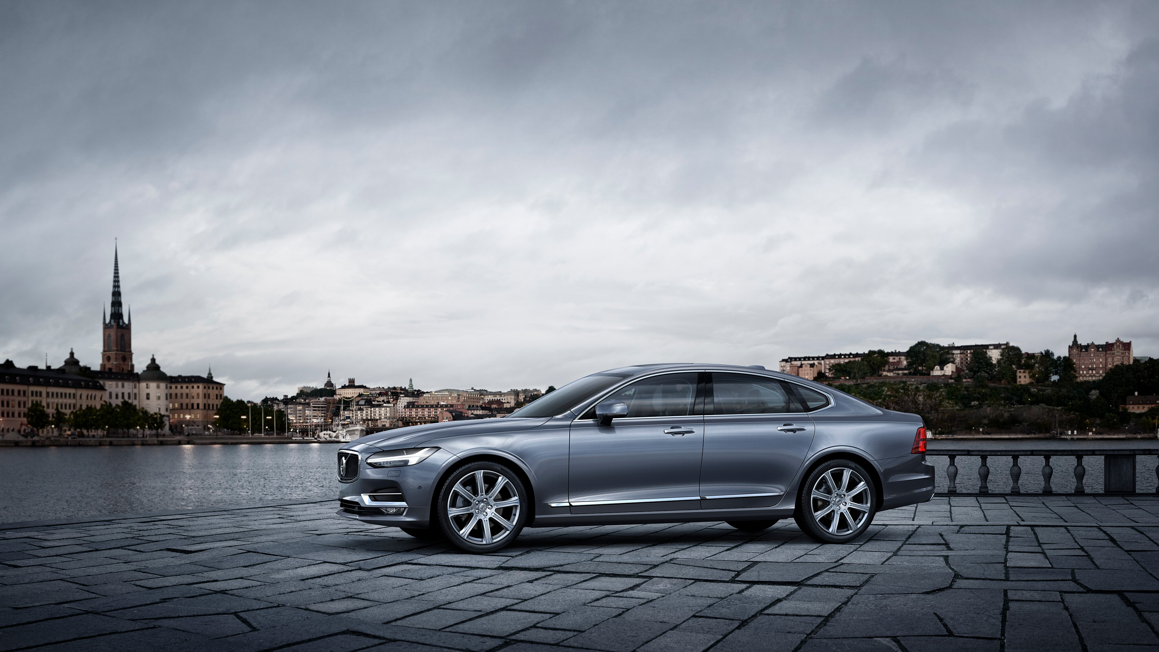 Side view of the Volvo S90 in metallic grey, parked next to a river in the city
