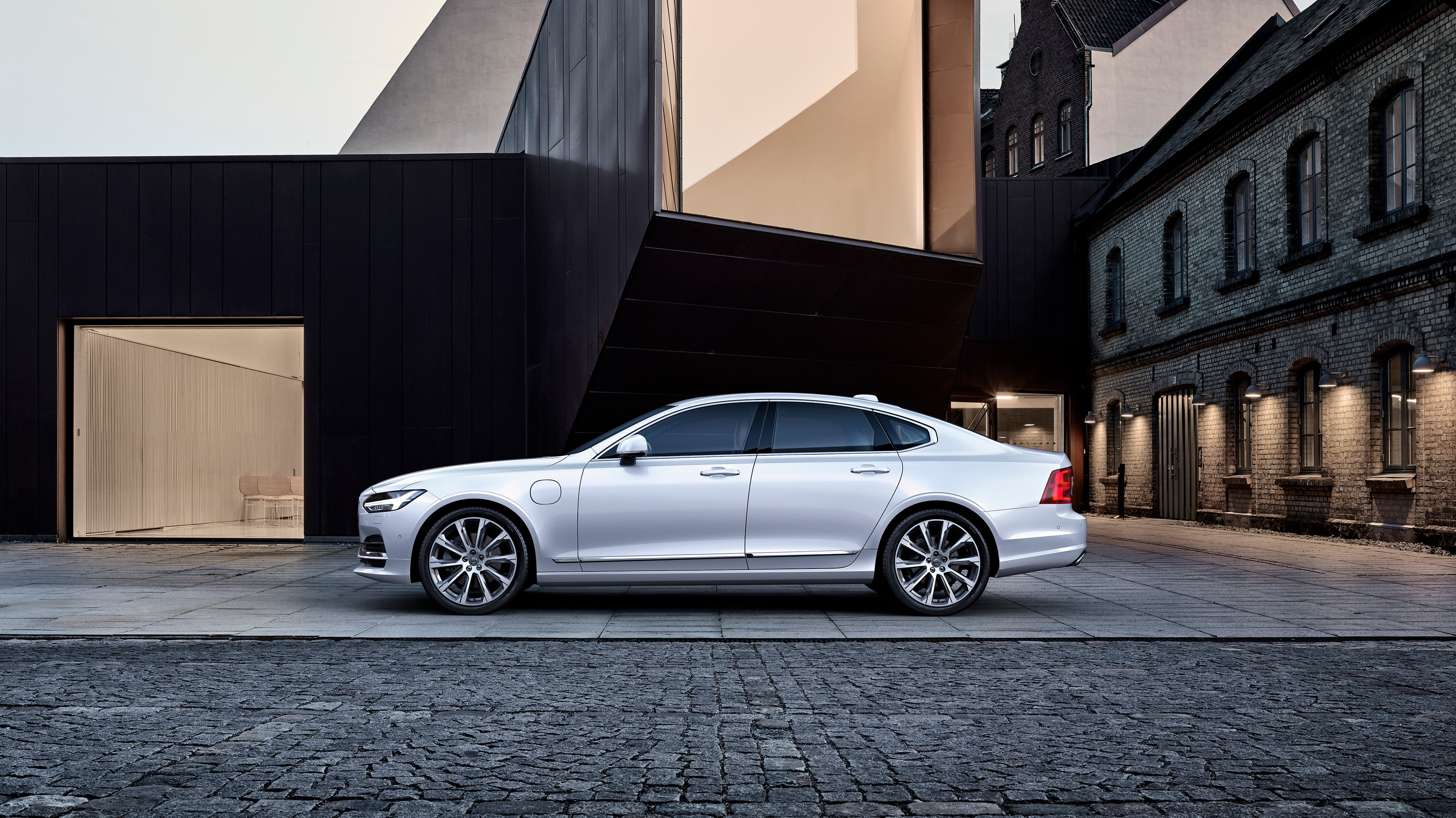 The Volvo S90 Excellence parked outside a modern building