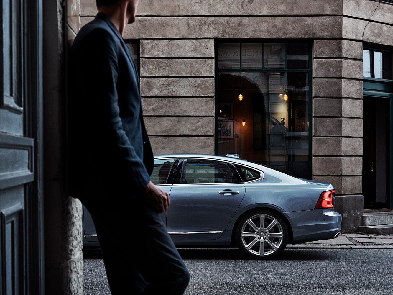 Side view of the rear of a Volvo S90 on a city street with a man reclining against a wall in the foreground