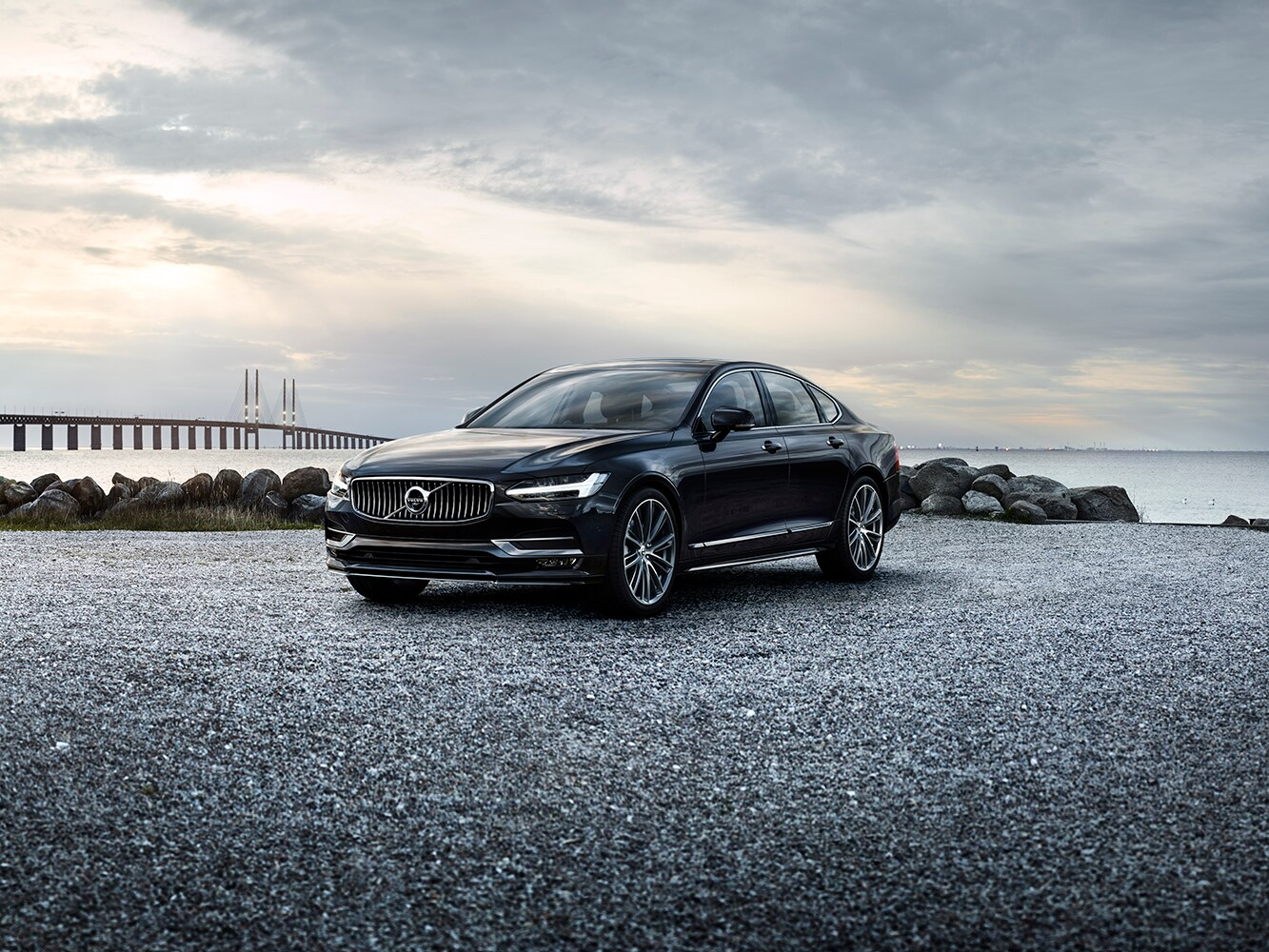 Front side view of the Volvo S90 in black parked on gravel