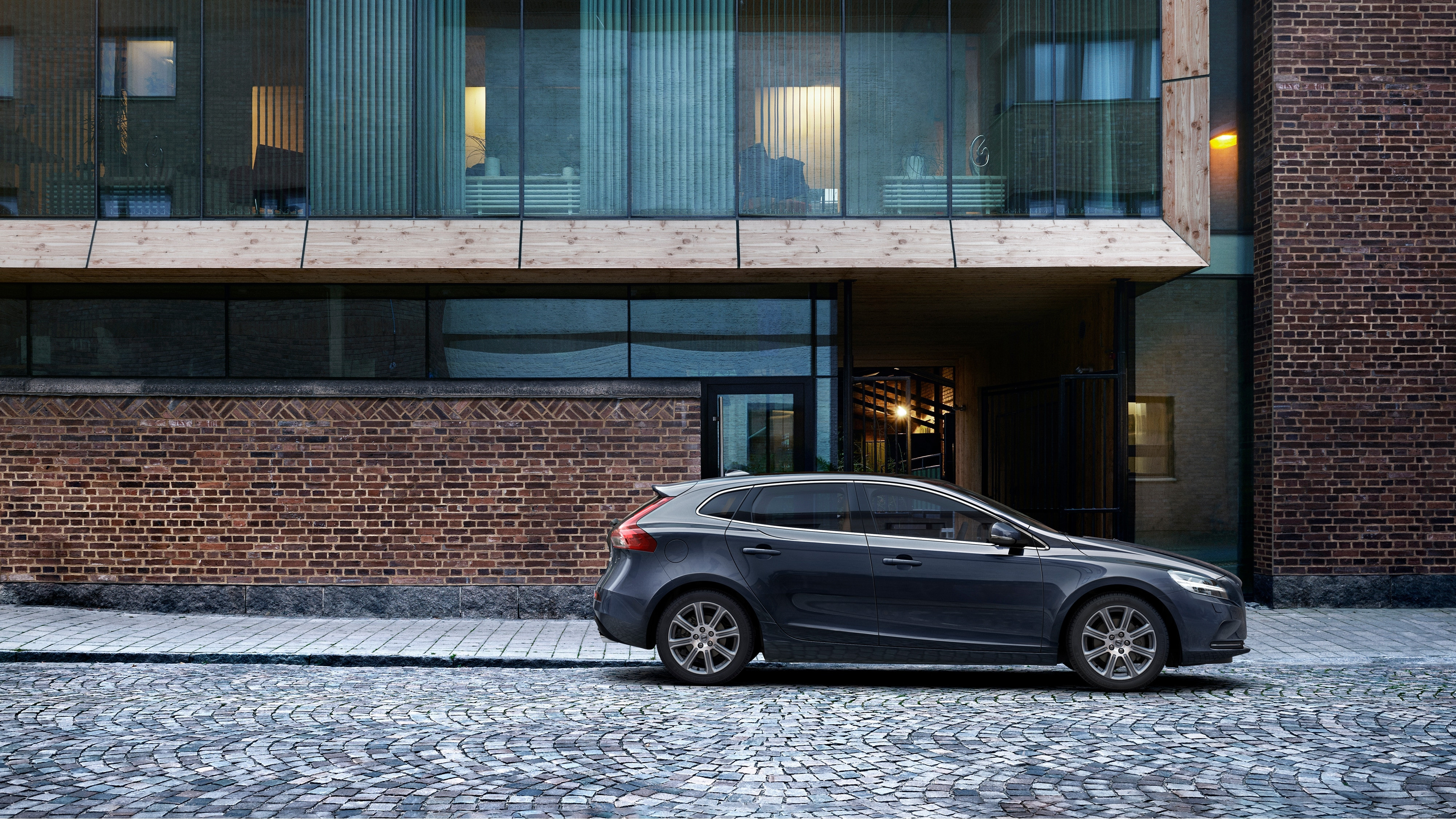 Side view of the Volvo V40 Inscription parked outside a modern building on a brick driveway