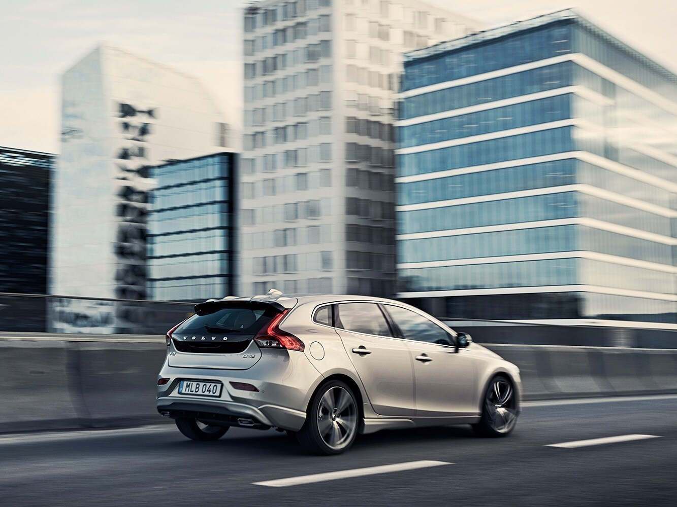 Back side view of Volvo V40 driving into the city on a highway with buildings in the background