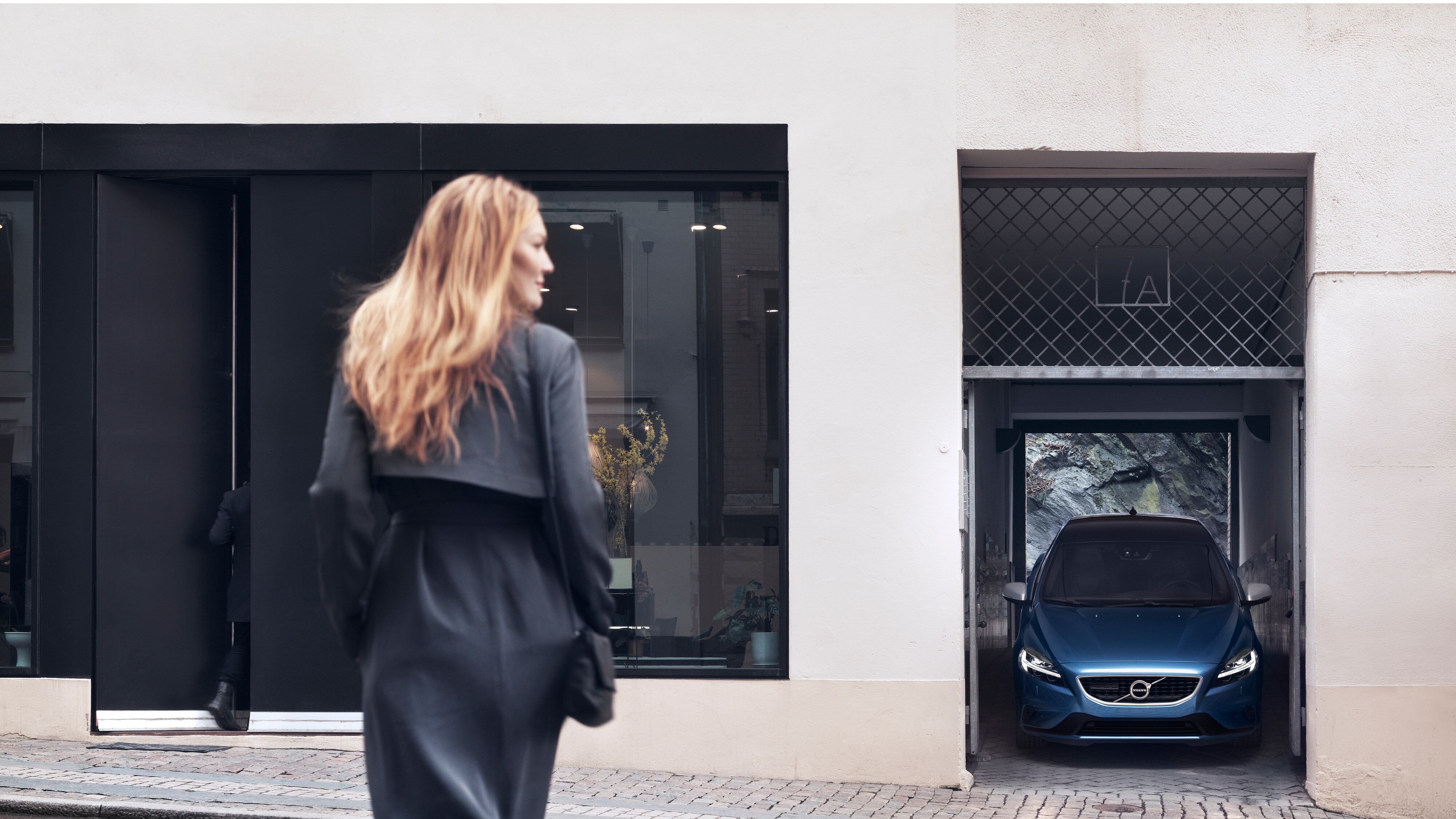 Woman crossing a road and the Volvo V40 R-Design parked in a narrow parking space between two buildings