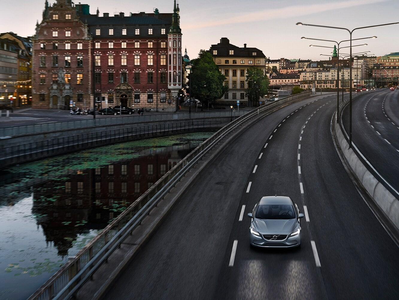 A Volvo V40 drives along a multi-lane road next to a city canal