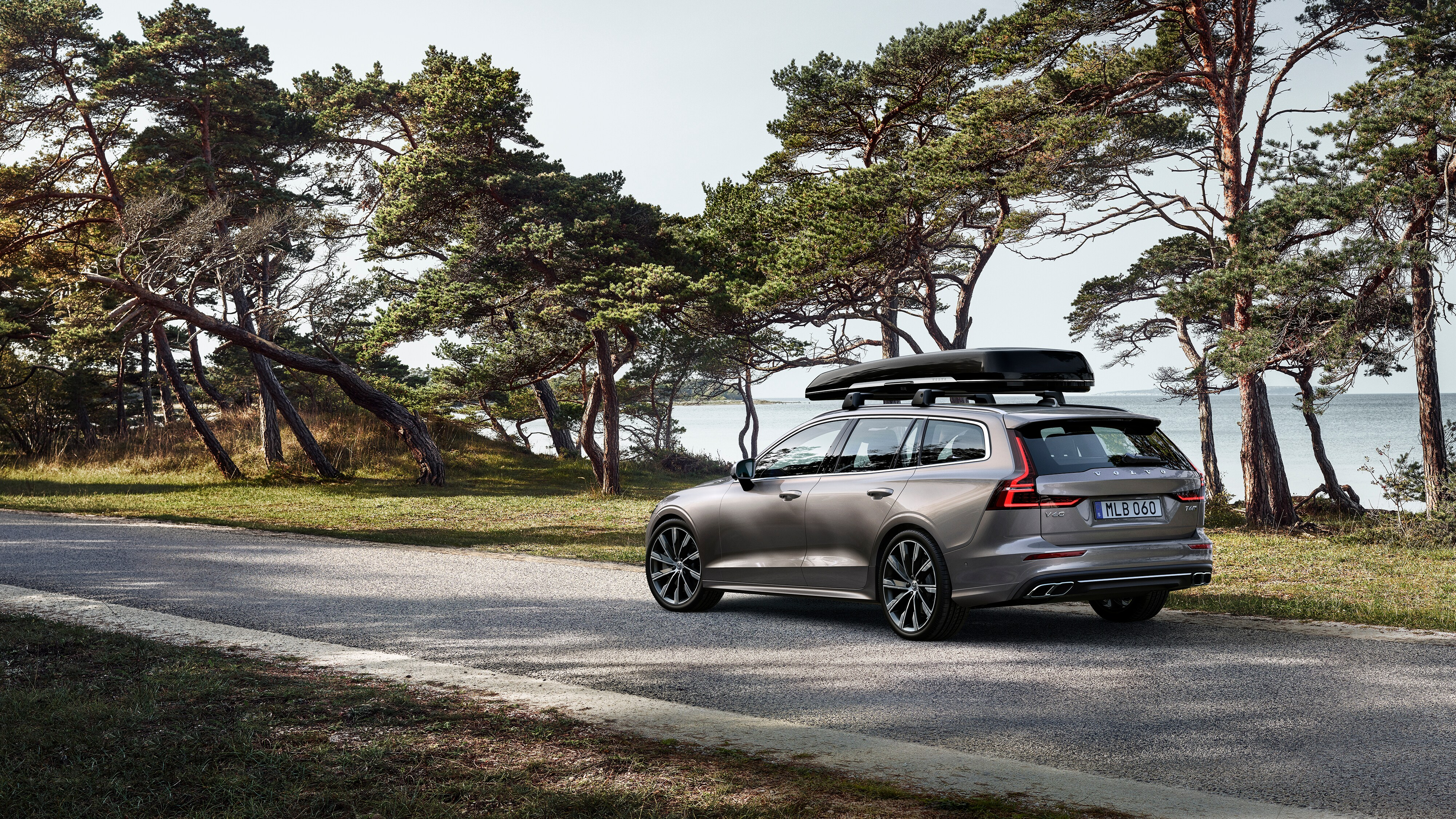 V60, equipped with a roofbox, travels down a country road