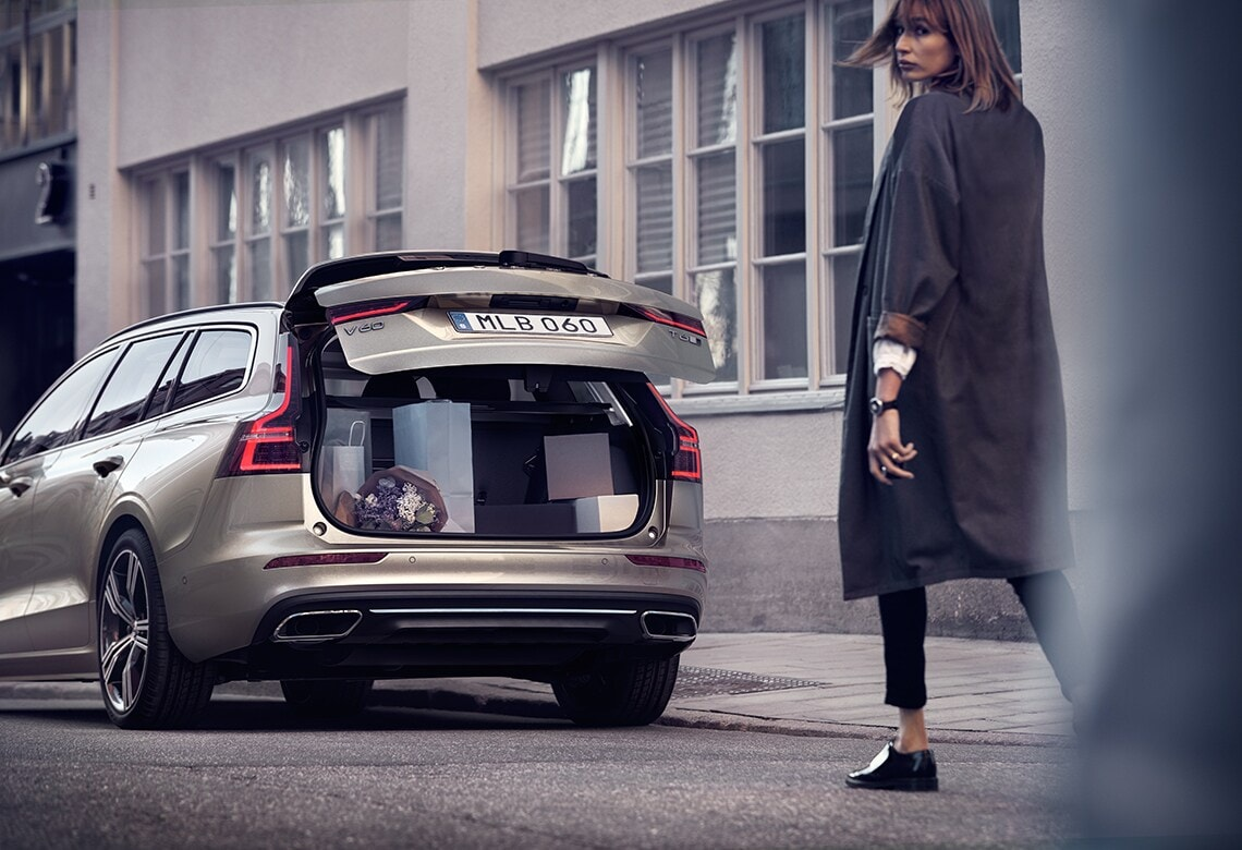 Woman walking behind Volvo V60