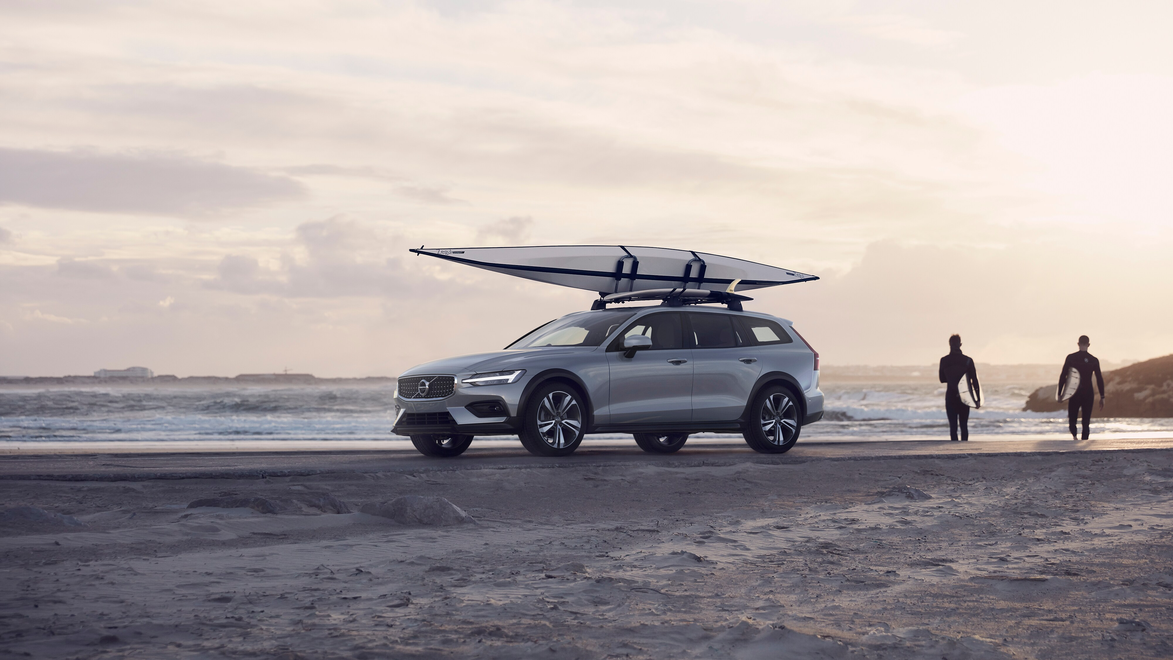 A Volvo V60 Cross Country parked on the beach at sunrise, with a canoe on