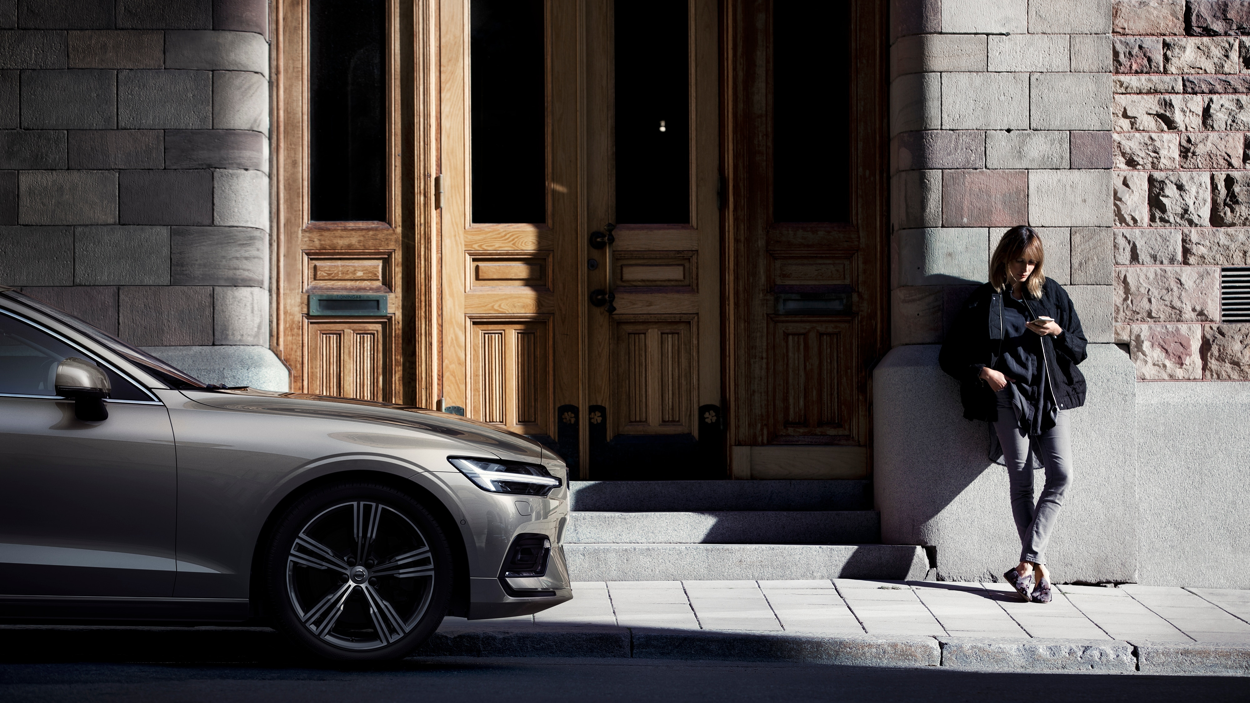 Young Volvo driver stands outside the entrance to an old building with her Volvo V60 parked on the street to her right.