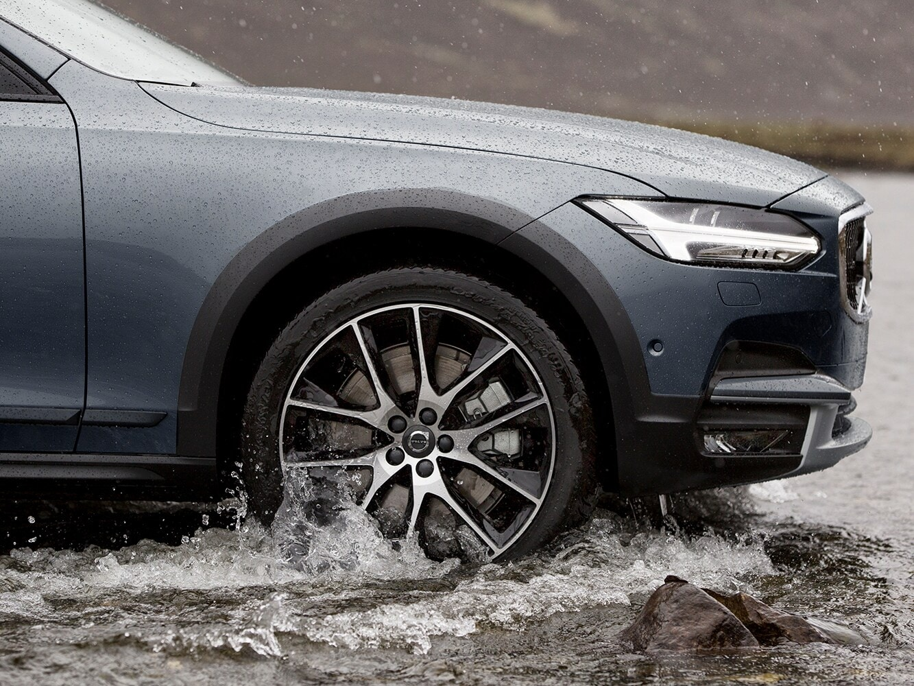 Close-up of front wheel of a Volvo V90 Cross Country fording a river showing the beautiful alloy wheels
