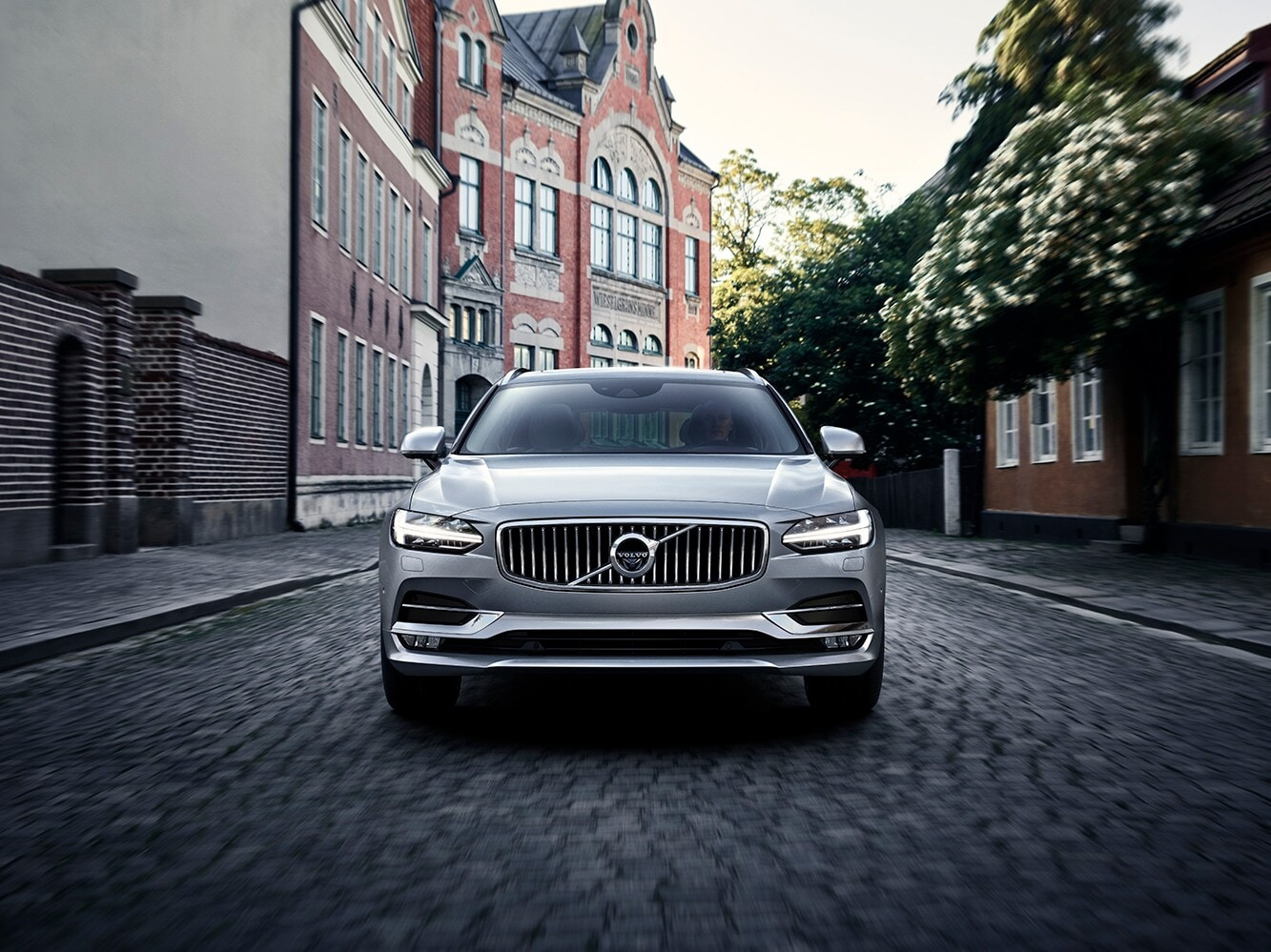Front view of the Volvo V90 driving down a cobbled road