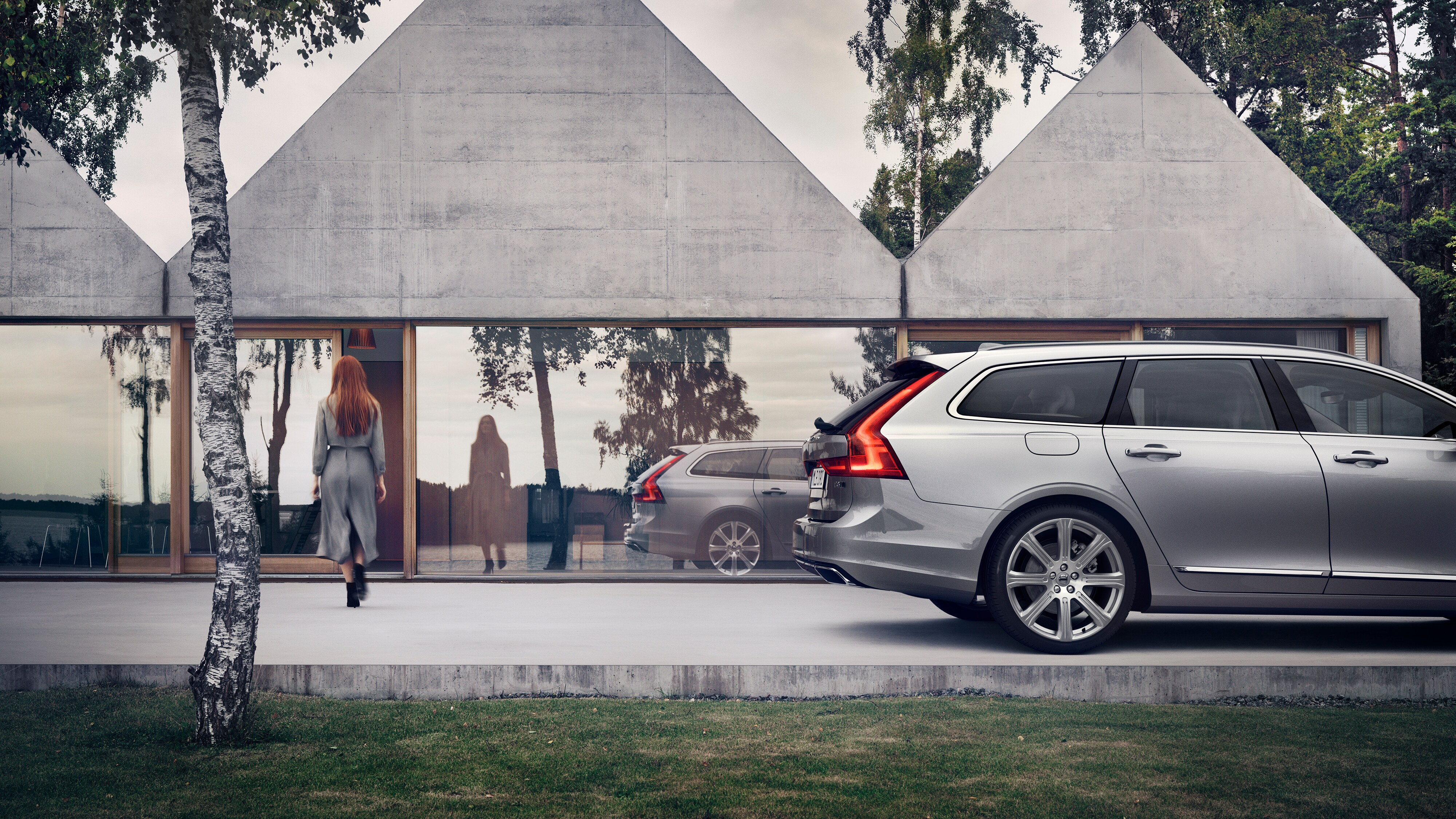 The Volvo V90 Esate car parked on a driveway of a modern home
