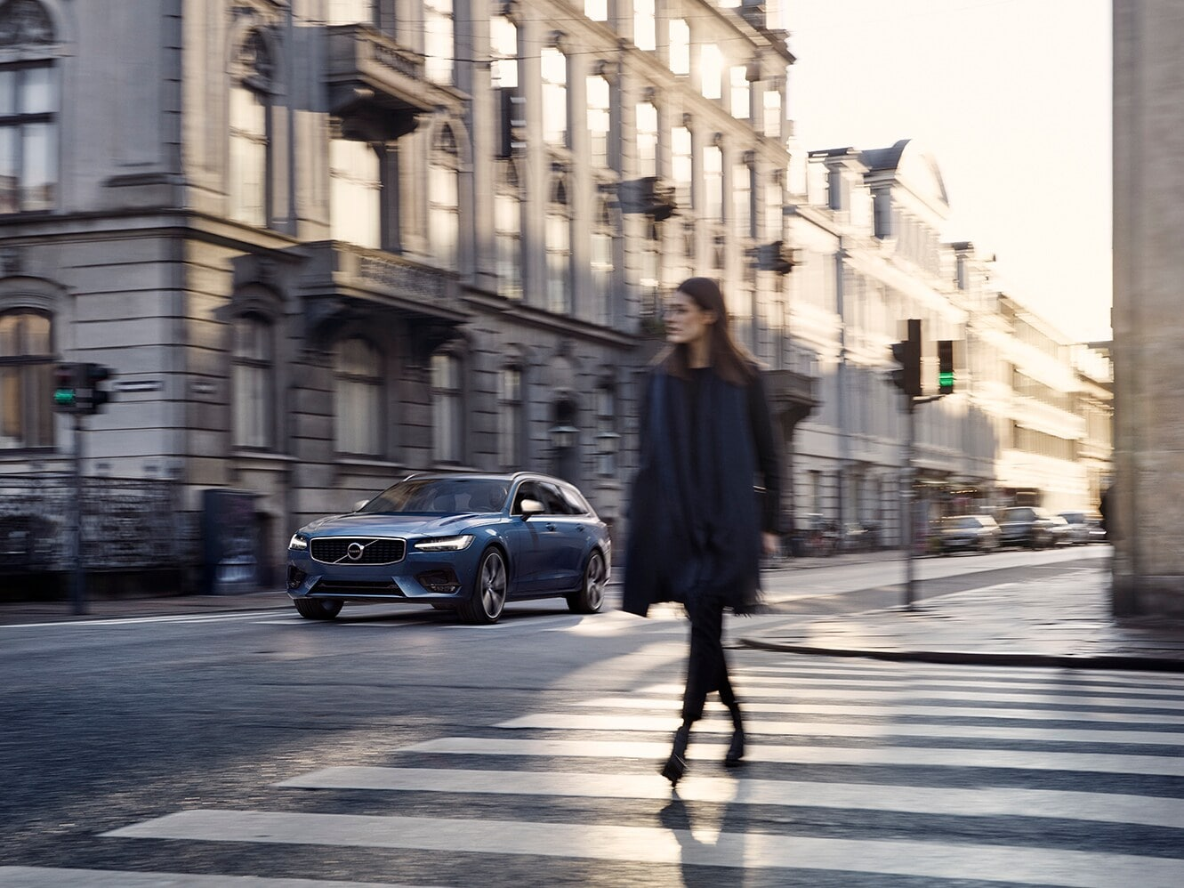 Woman crosses road whilst Volvo V90 R-Design passes in background