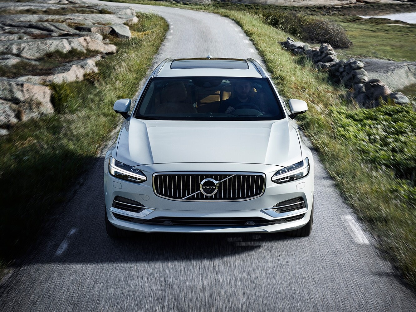 Front view of a Volvo V90 driving along a country road