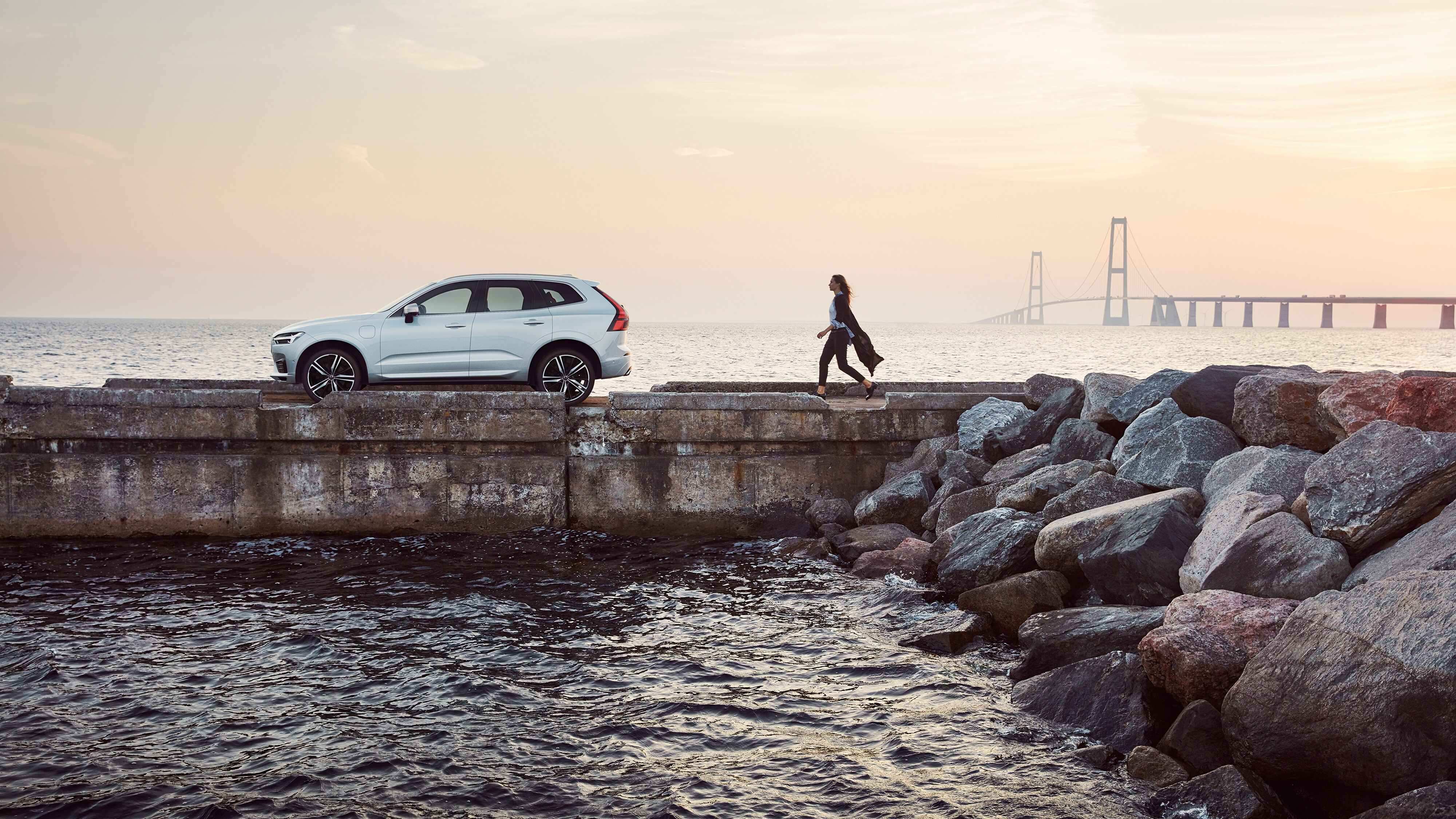 Side view of the new Volvo XC60 R-Design parked on a jetty with a woman approaching it