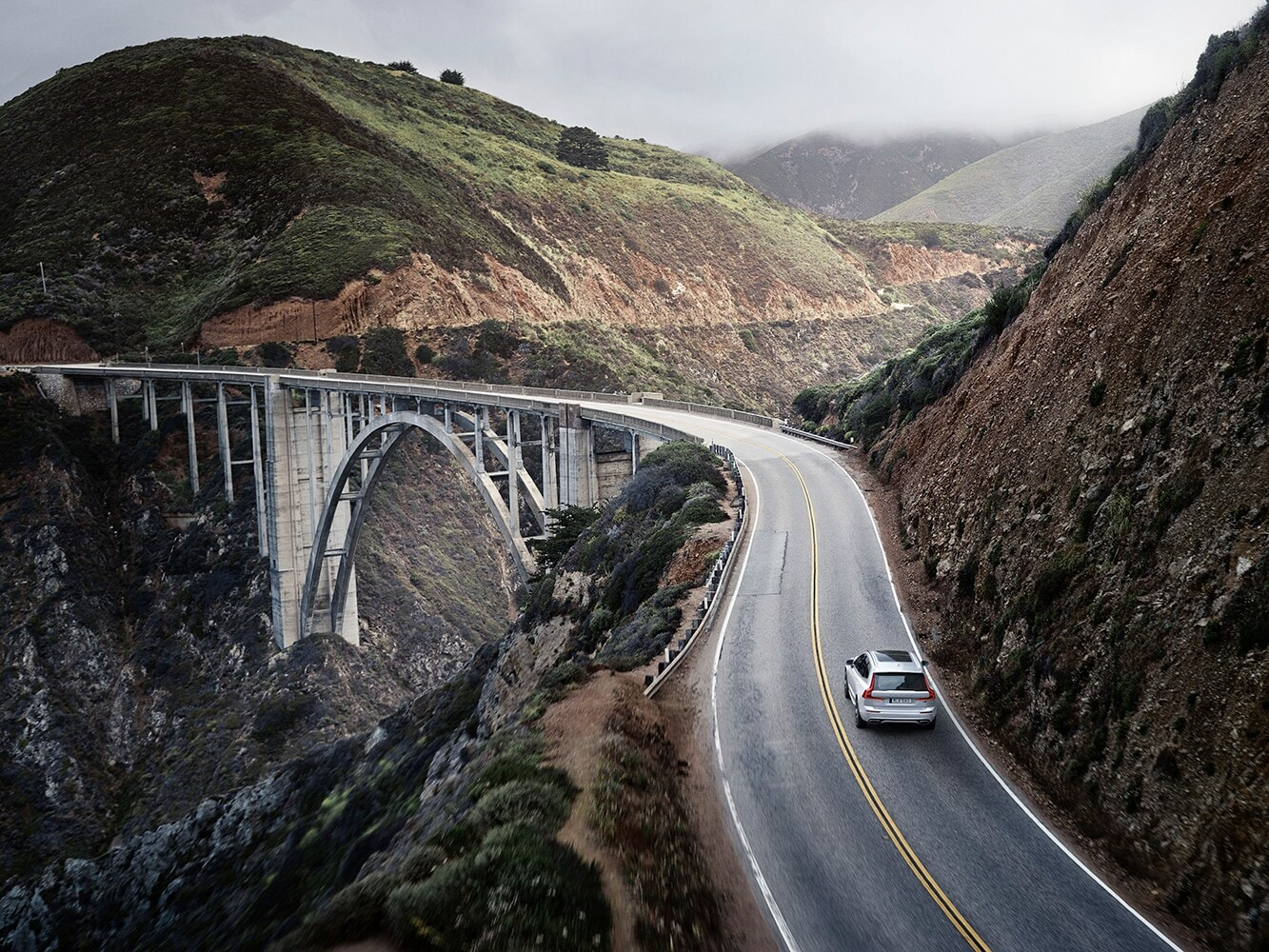 The new Volvo XC60 R-Design driving along a mountain road towards a bridge