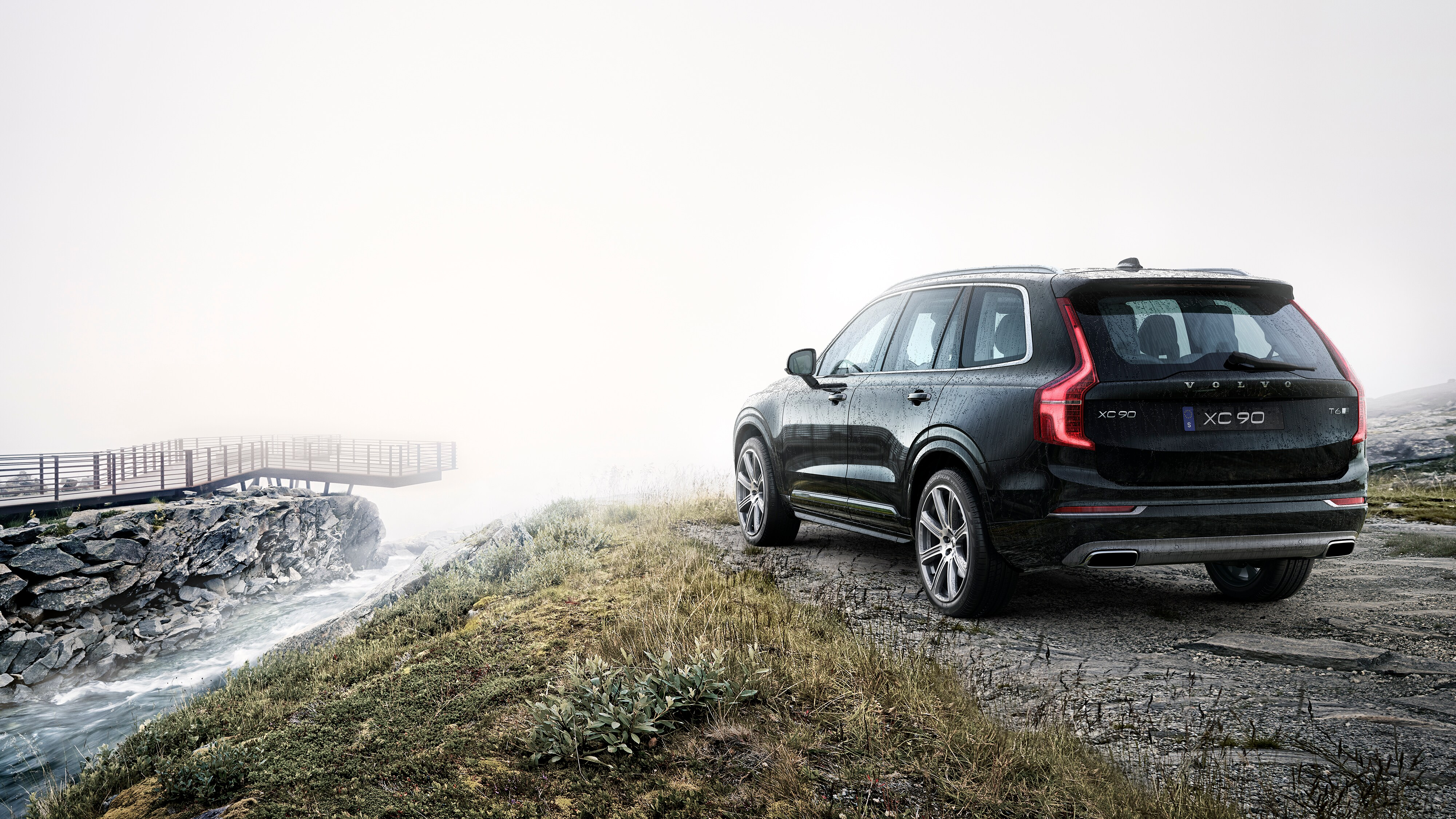 A Volvo XC90 parked next to a fast-flowing stream in the countryside
