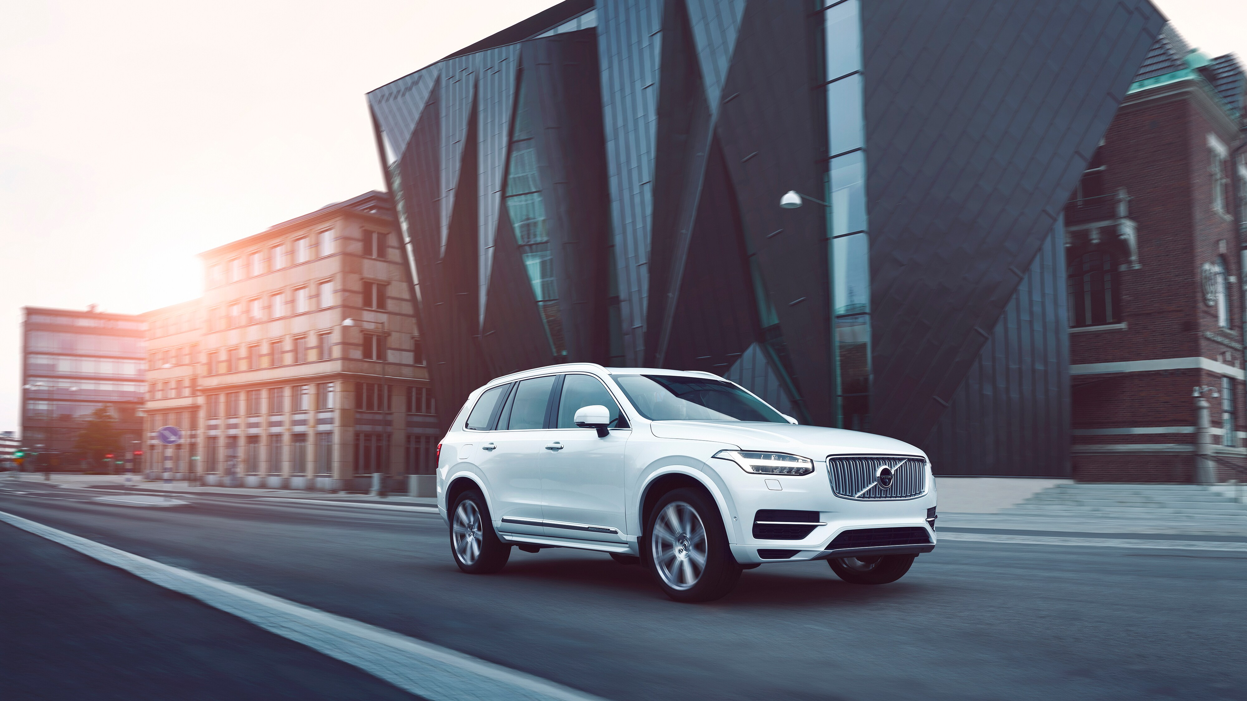 The Volvo XC90 drives past a modern building