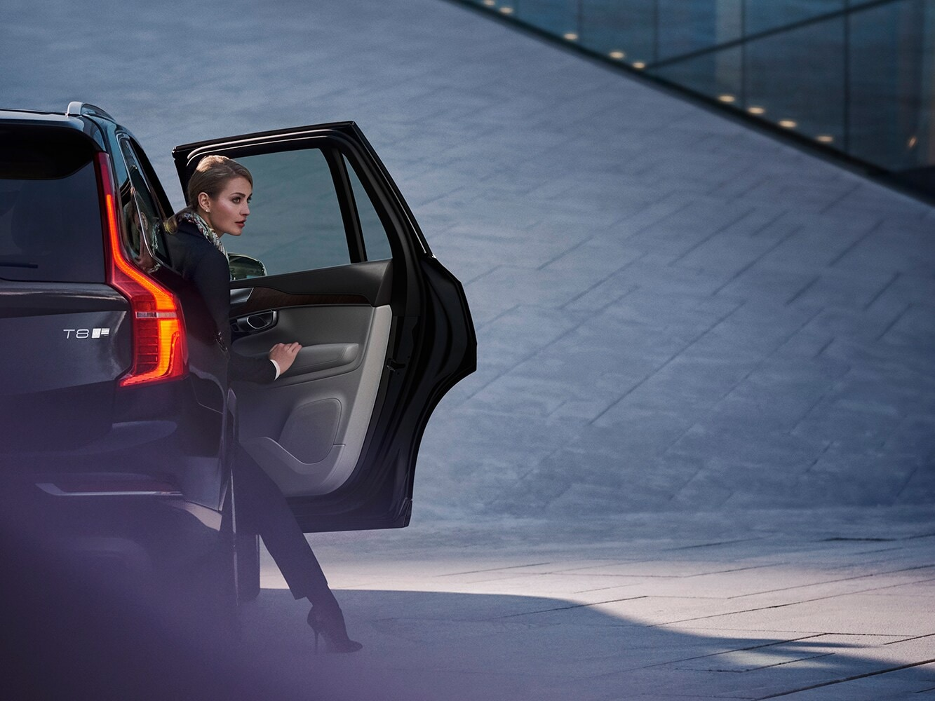 Woman exits from the passenger side door of a Volvo XC90