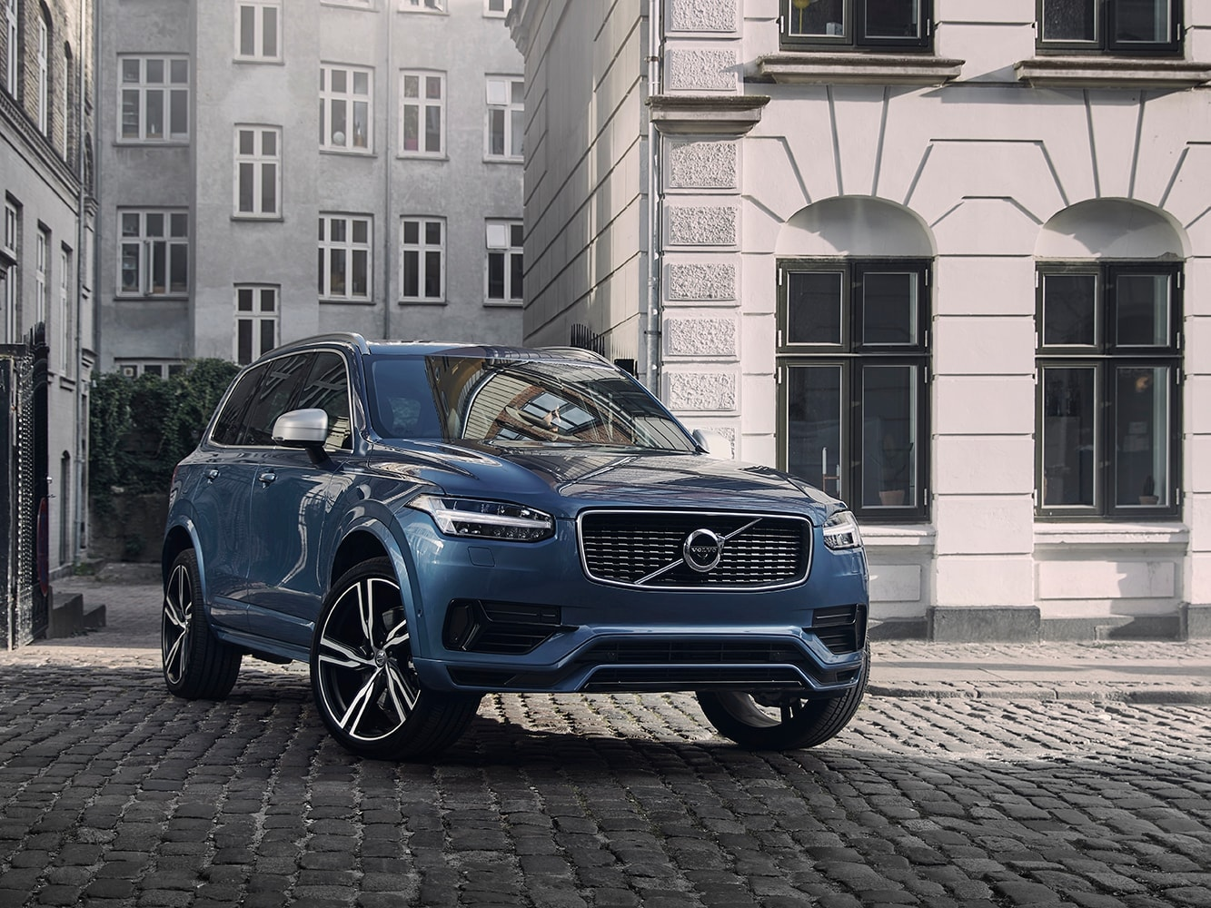 Front side view of a Volvo XC90 R-Design parked on a cobbled street