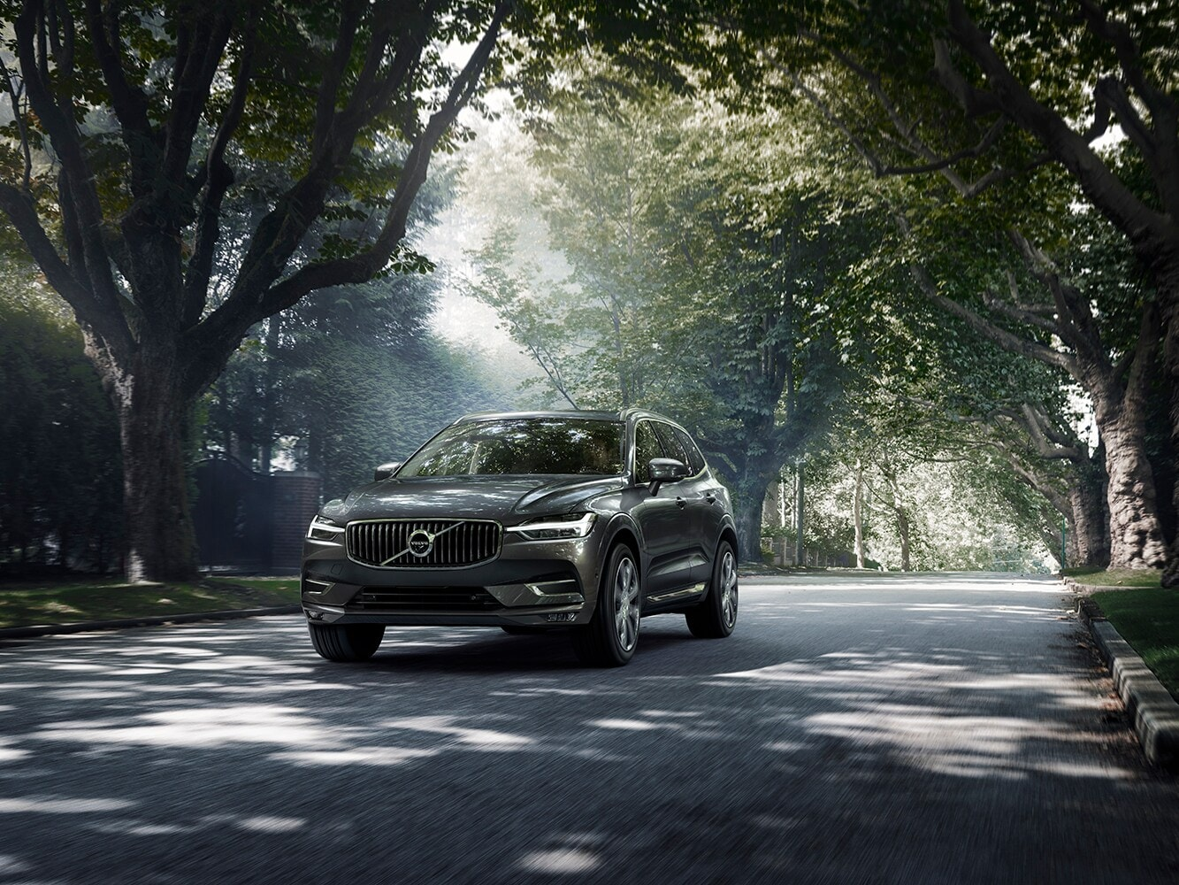 A Volvo XC60 drives down a tree-lined road