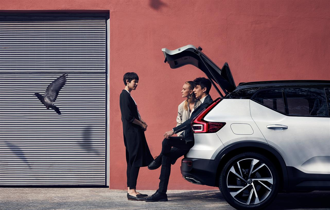 People sitting in the back of a parked Volvo XC40 compact SUV