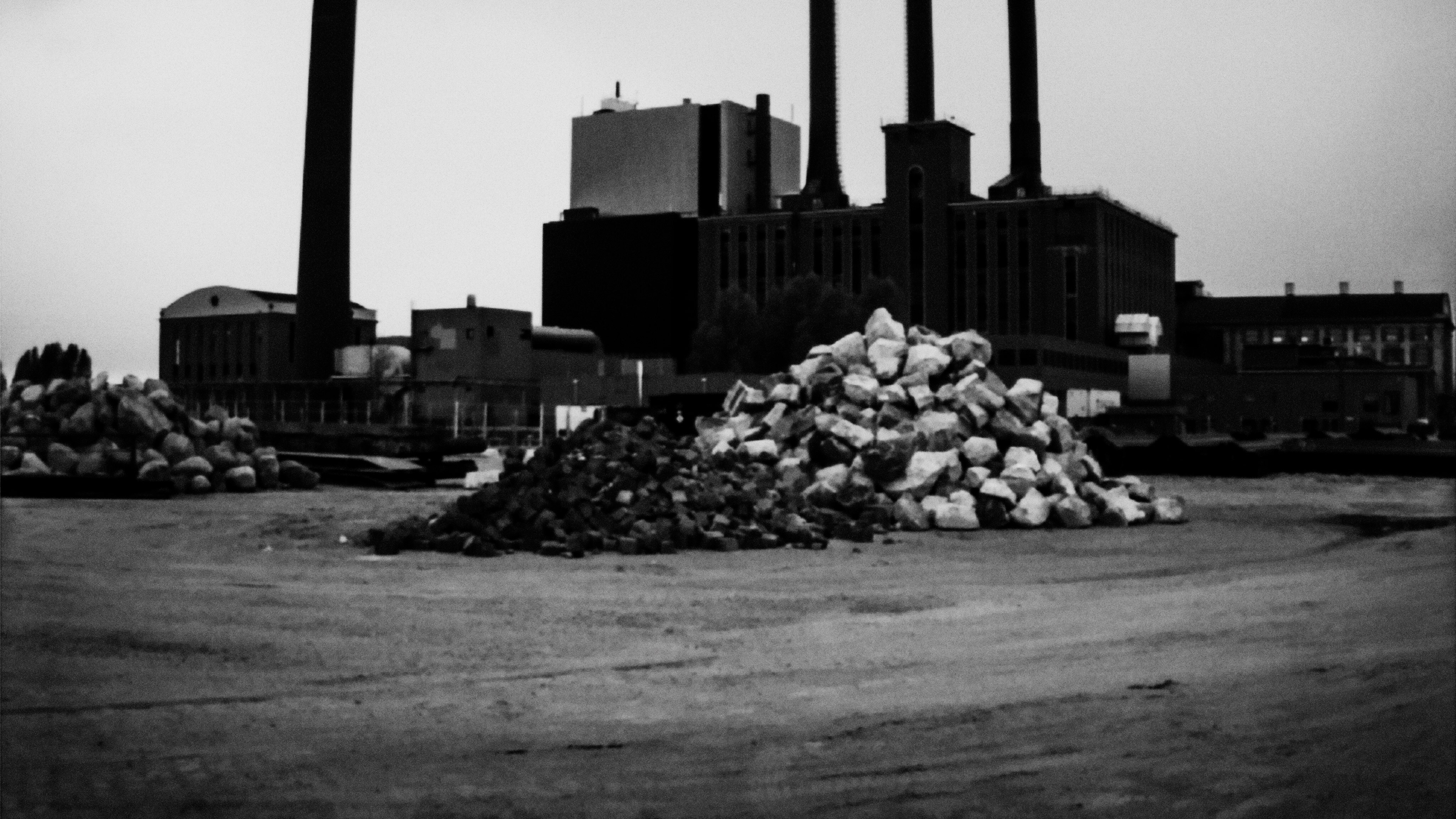 Pile of stones in front of industry building