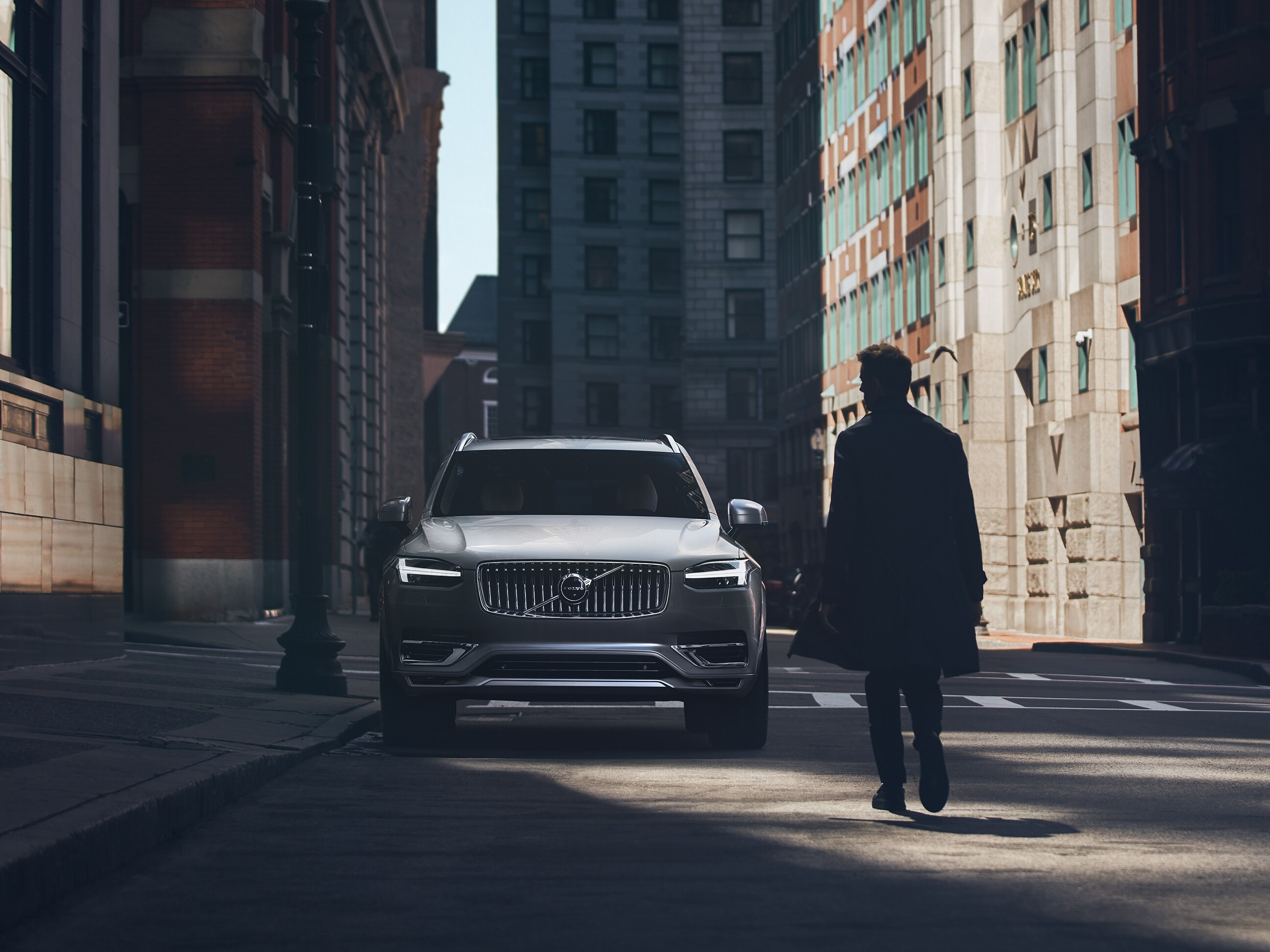A man walks towards a Volvo XC90 parked on a city street