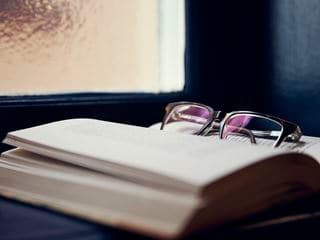 A close up of Hans Rosenfeldt's glasses lying on an open book