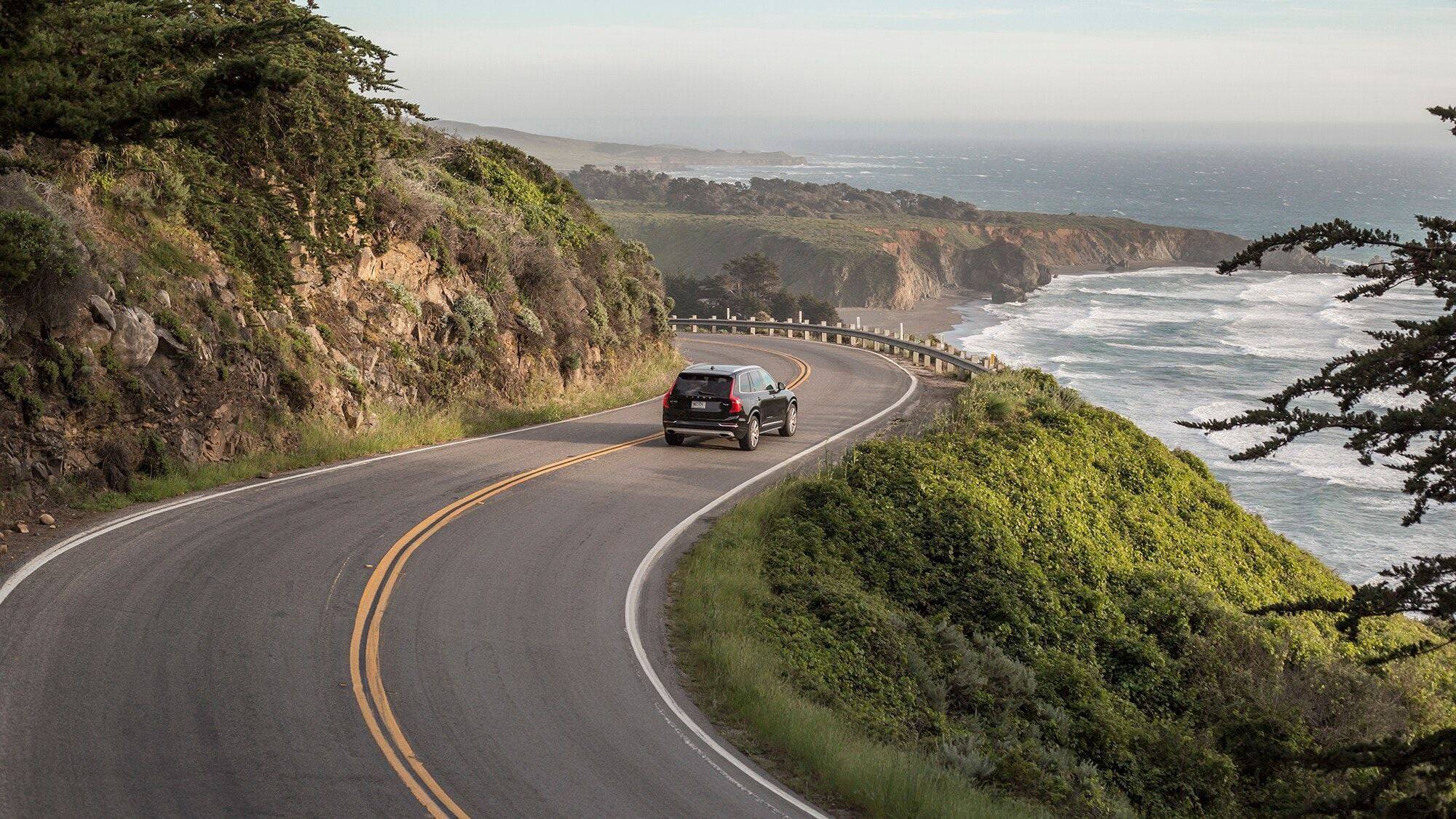 The new Volvo XC90 winds along the road of the Californian coast