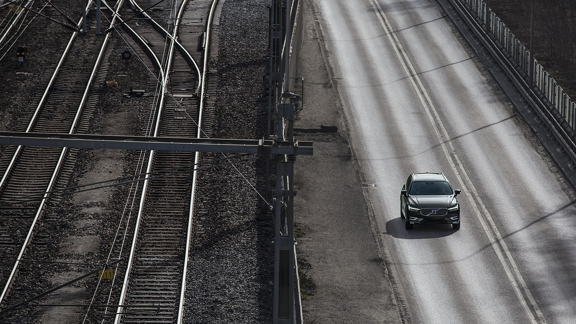 The New Volvo XC60 drives alongside a section of overground rail.