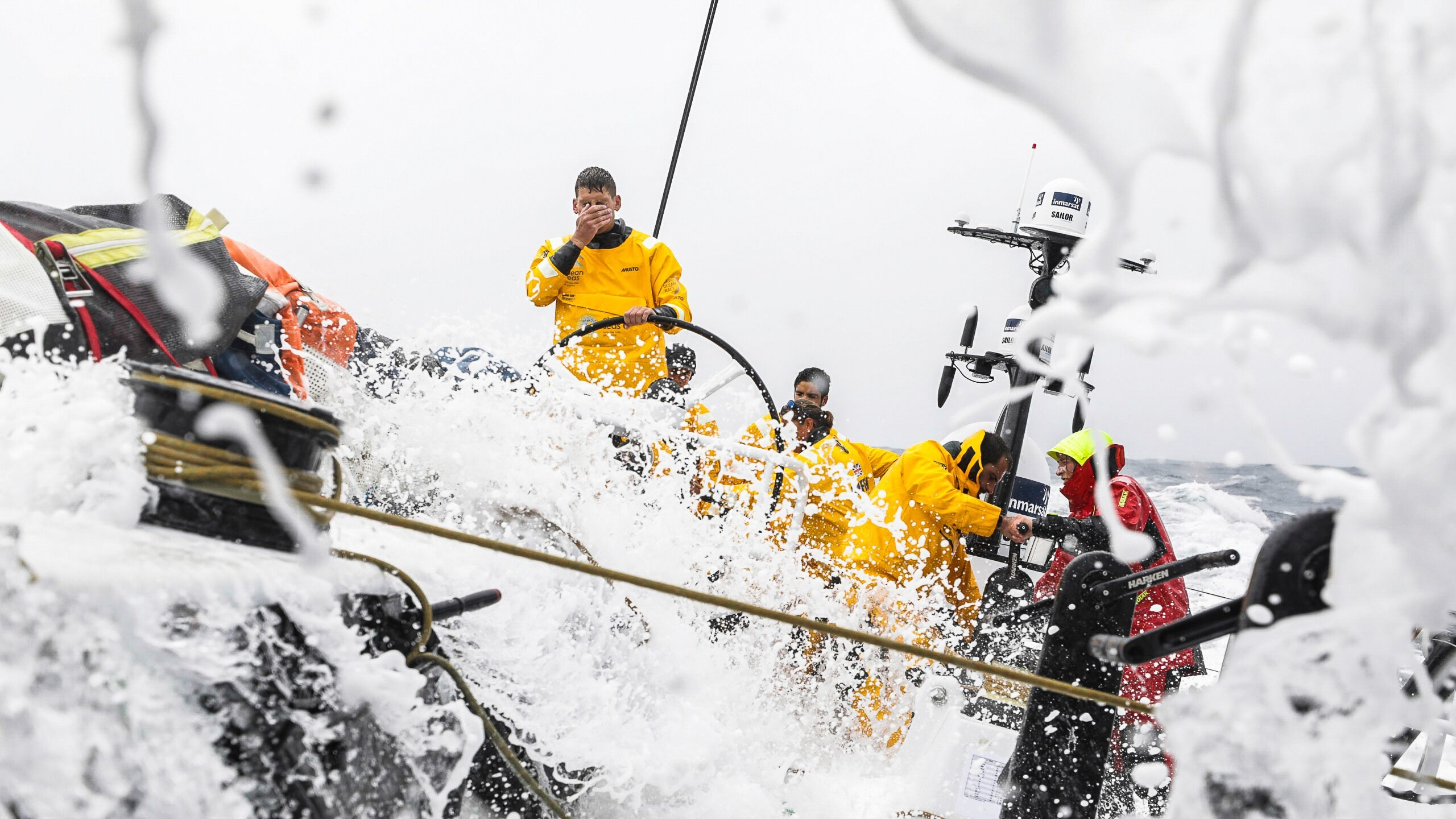 A crew at work in stormy seas, with waves crashing over the deck