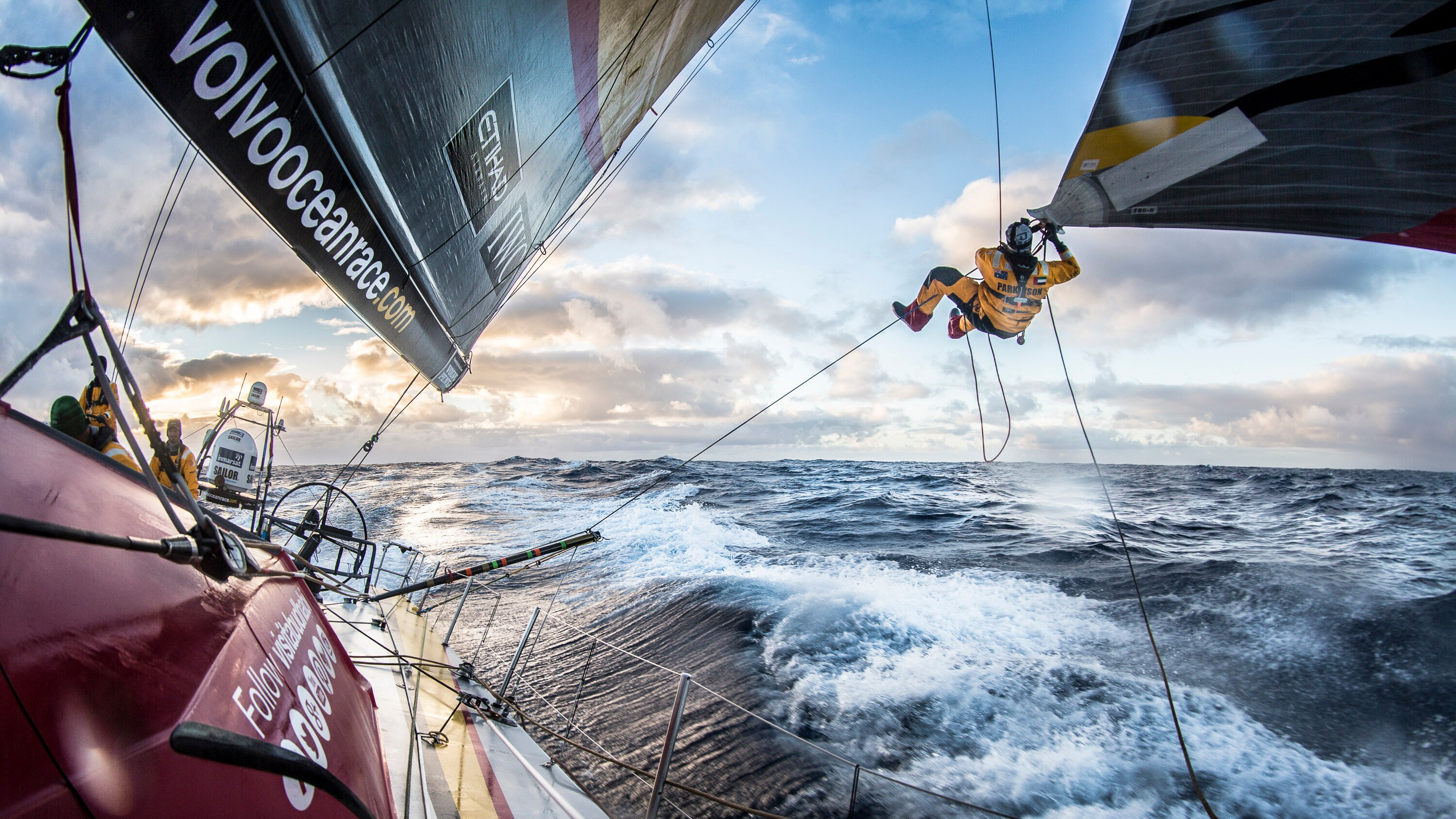 A Volvo Ocean Race crew member tackles a tricky rope climb out on the ocean
